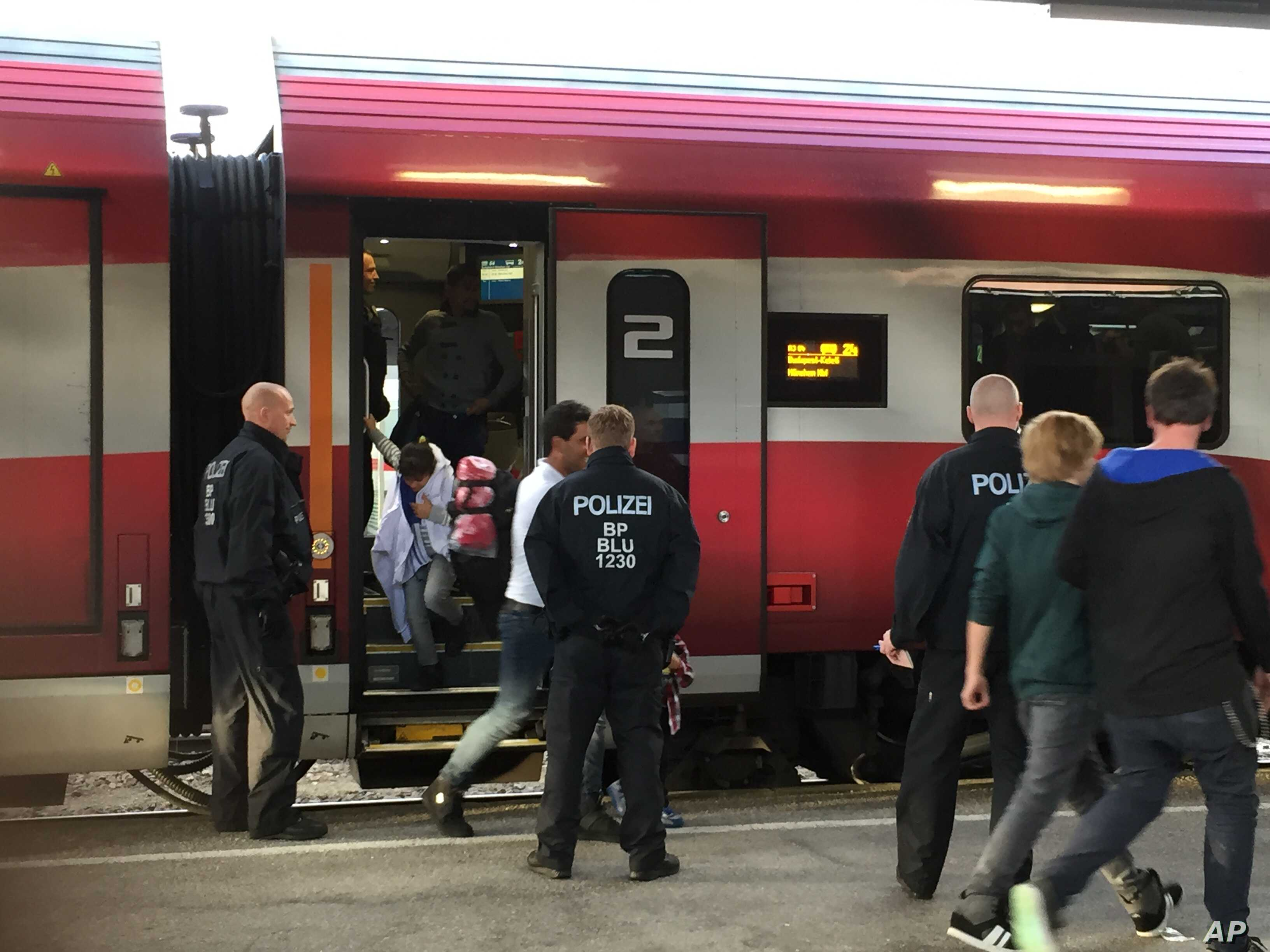 German police pull migrants off a train from Budapest and Vienna as part of new border control measures meant to ease the pressure on Munich, until now the main entry point for migrants reaching Germany, Sept. 14, 2015. (L. Ramirez/VOA)