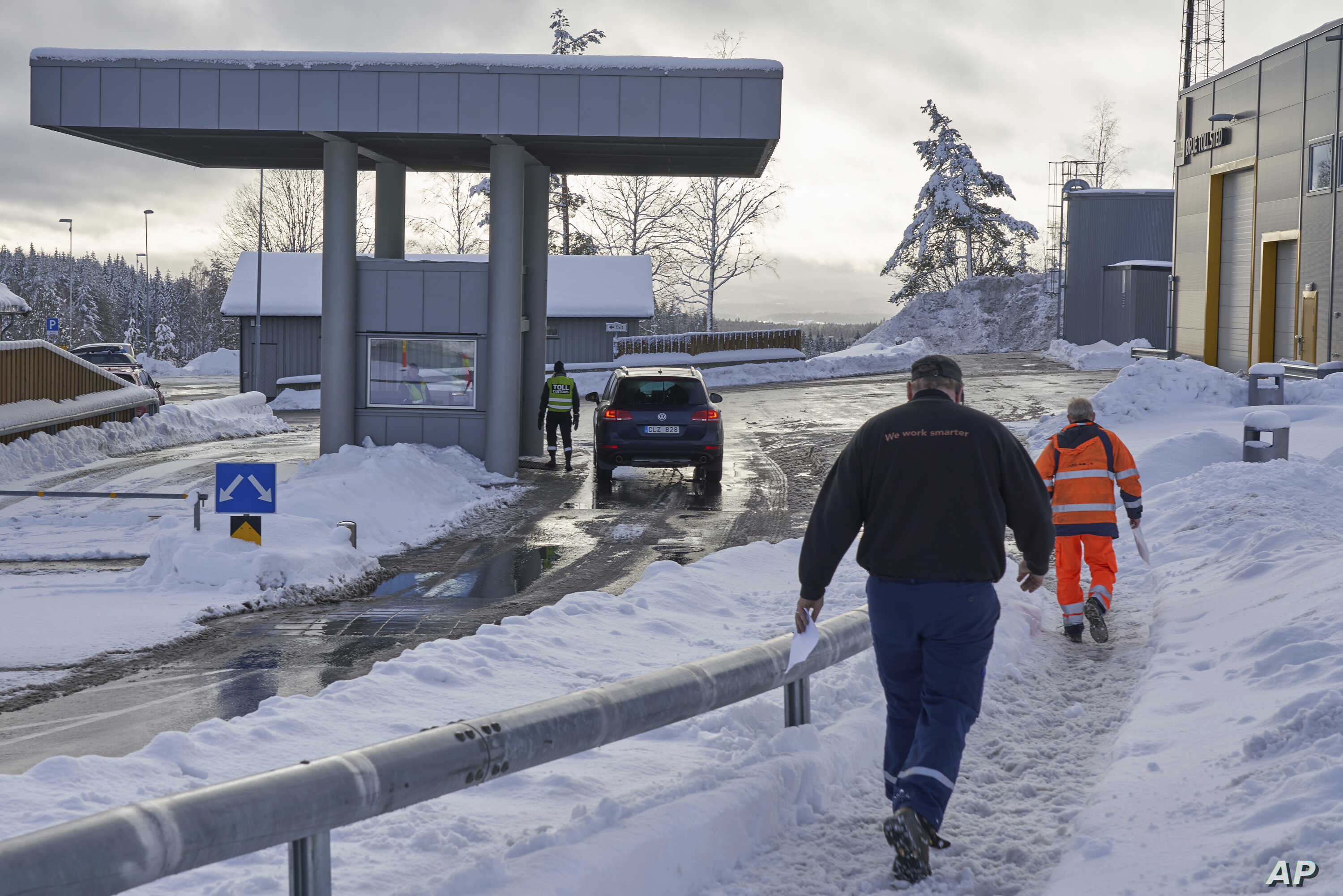 Truck drivers with customs clearance documents walk toward the Norwegian Customs office at the Orje border as officers perform checks on cars entering from Sweden, Feb. 8 2019.