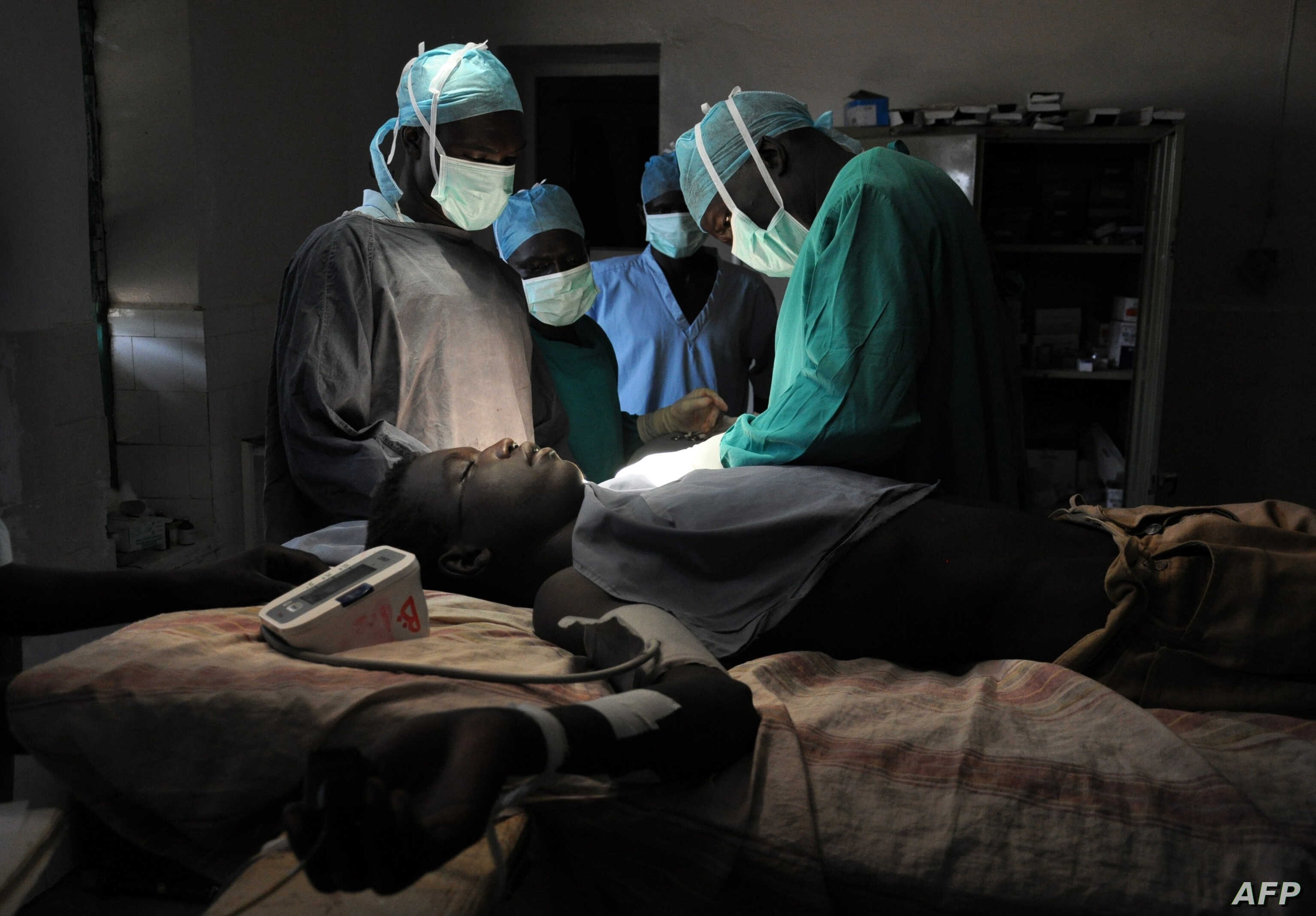 FILE - Evan Atar Adaha performs a surgery on a Sudanese youth at a hospital in Kurmuk region of Sudan's Blue Nile state, Oct. 10, 2011.