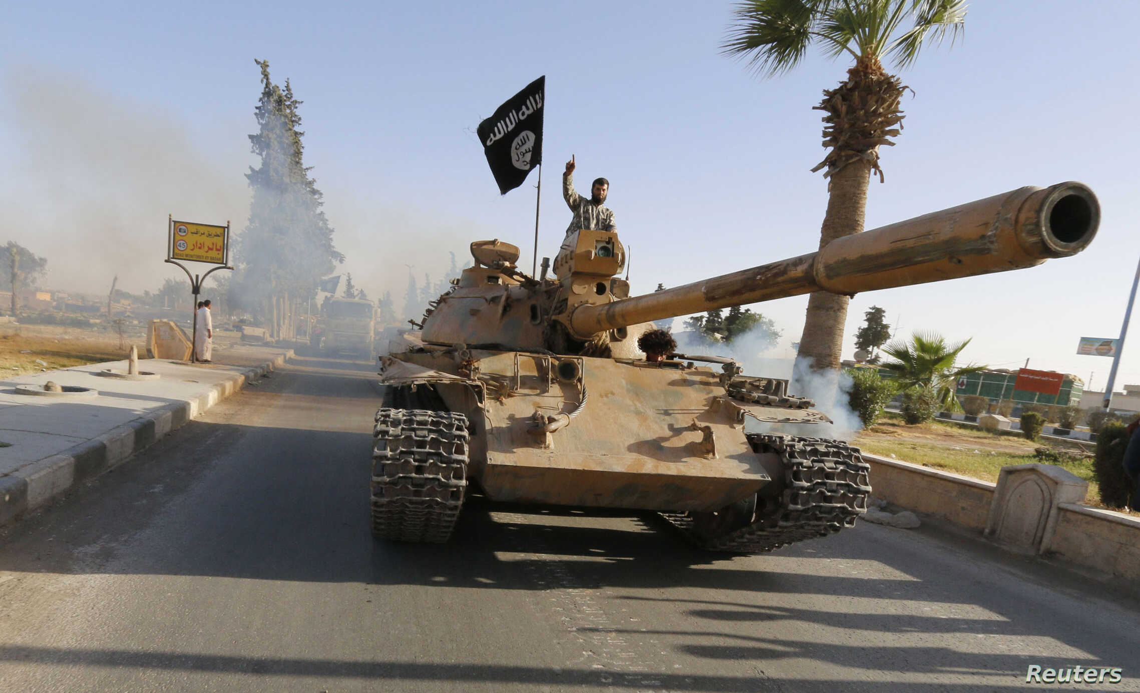 FILE - Militant Islamist fighters on a tank take part in a military parade along the streets of northern Raqqa province.