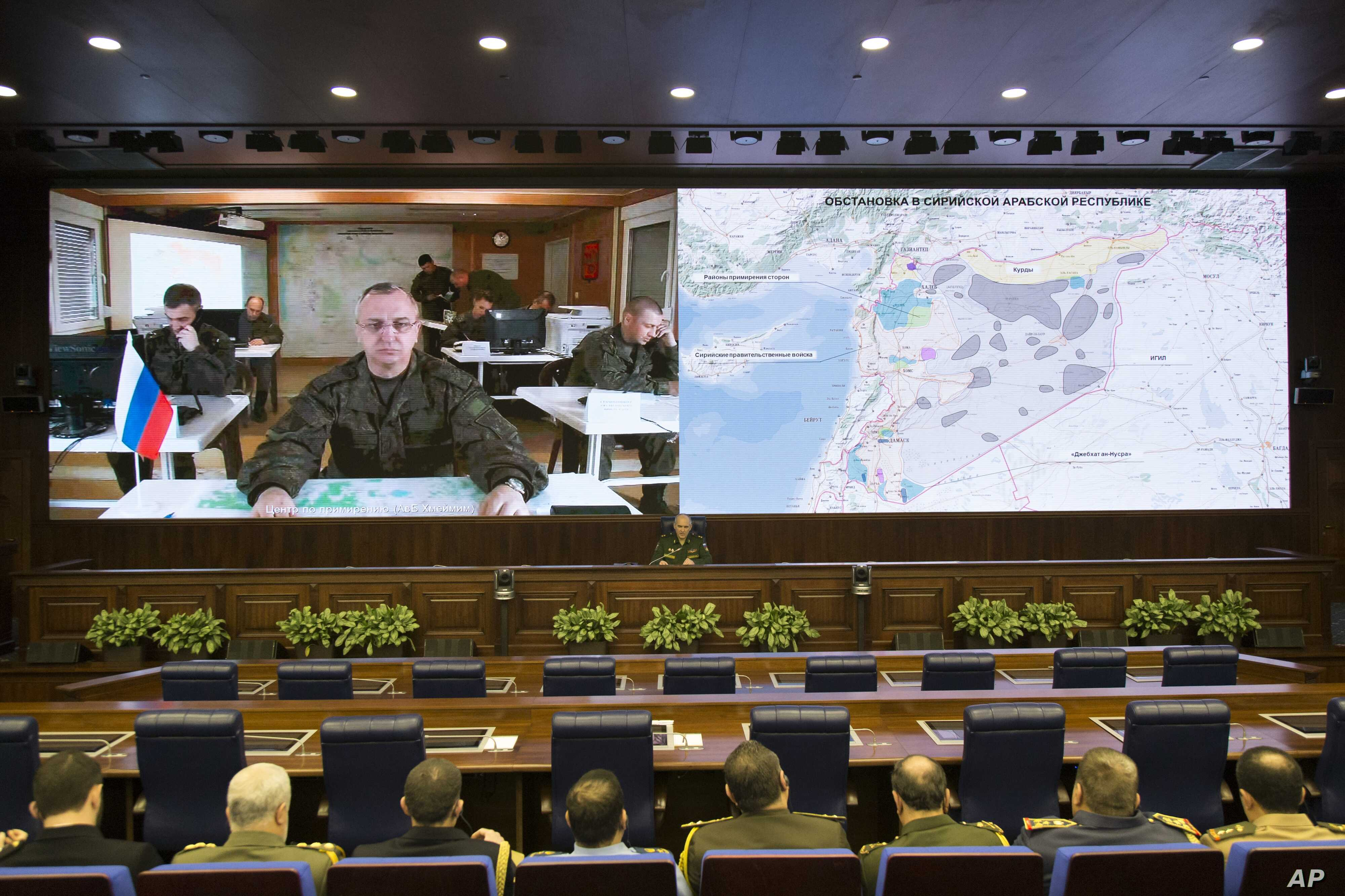 Lt.-Gen. Sergei Rudskoi of the Russian Military General Staff, background center, speaks to the media in Moscow, Feb. 27, 2016. A top military official said Russia has halted airstrikes in areas where armed groups said they would abide by a cease-fir...