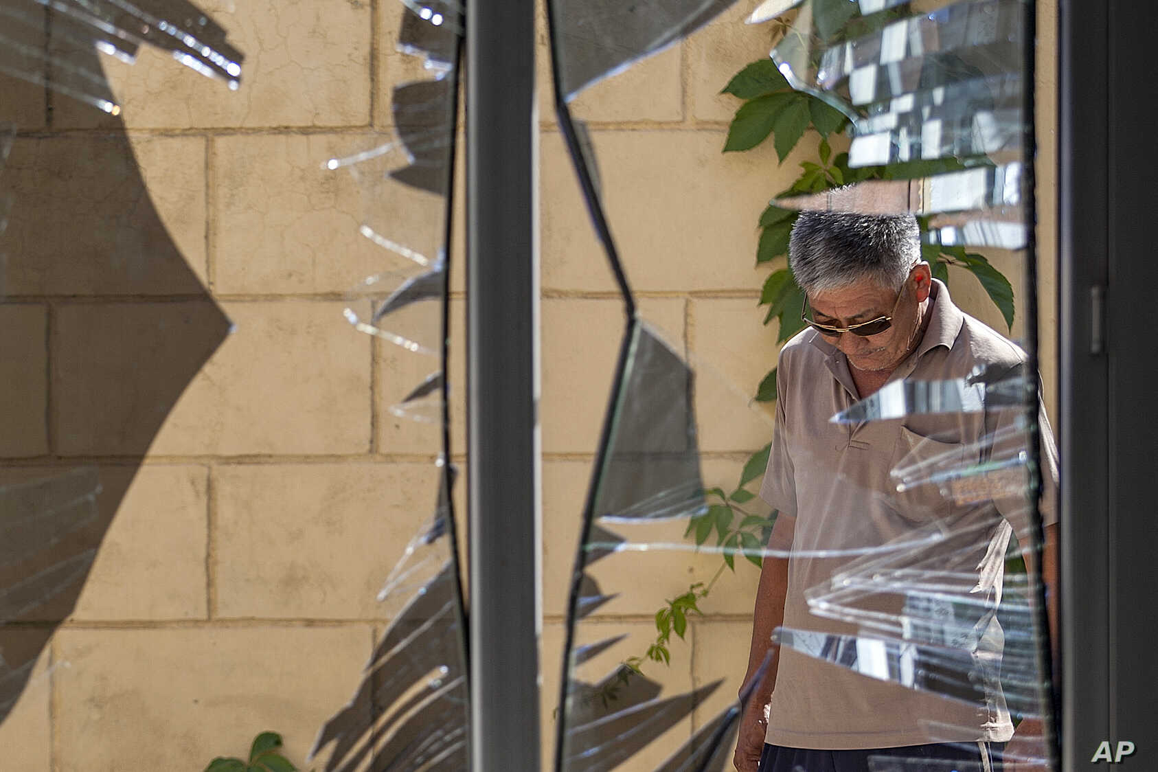 FILE - A Chinese Embassy employee examines broken windows, Aug. 30, 2016, after a suicide bombing in Bishkek, Kyrgyzstan. The bombing highlighted the threat of an ethnic Uighur militant group and the growing Chinese involvement in Syria and Afghanis...
