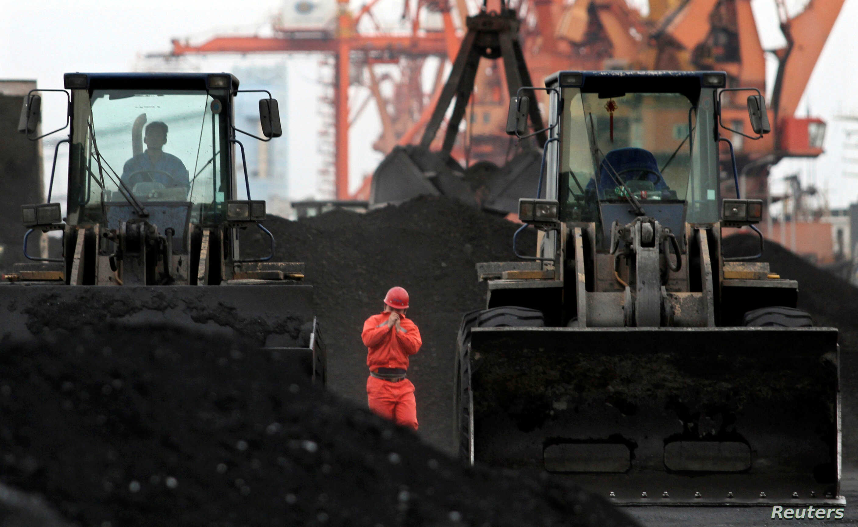 An employee walks between front-end loaders which are used to move coal imported from North Korea at Dandong port in the Chinese border city of Dandong, Dec. 7, 2010.