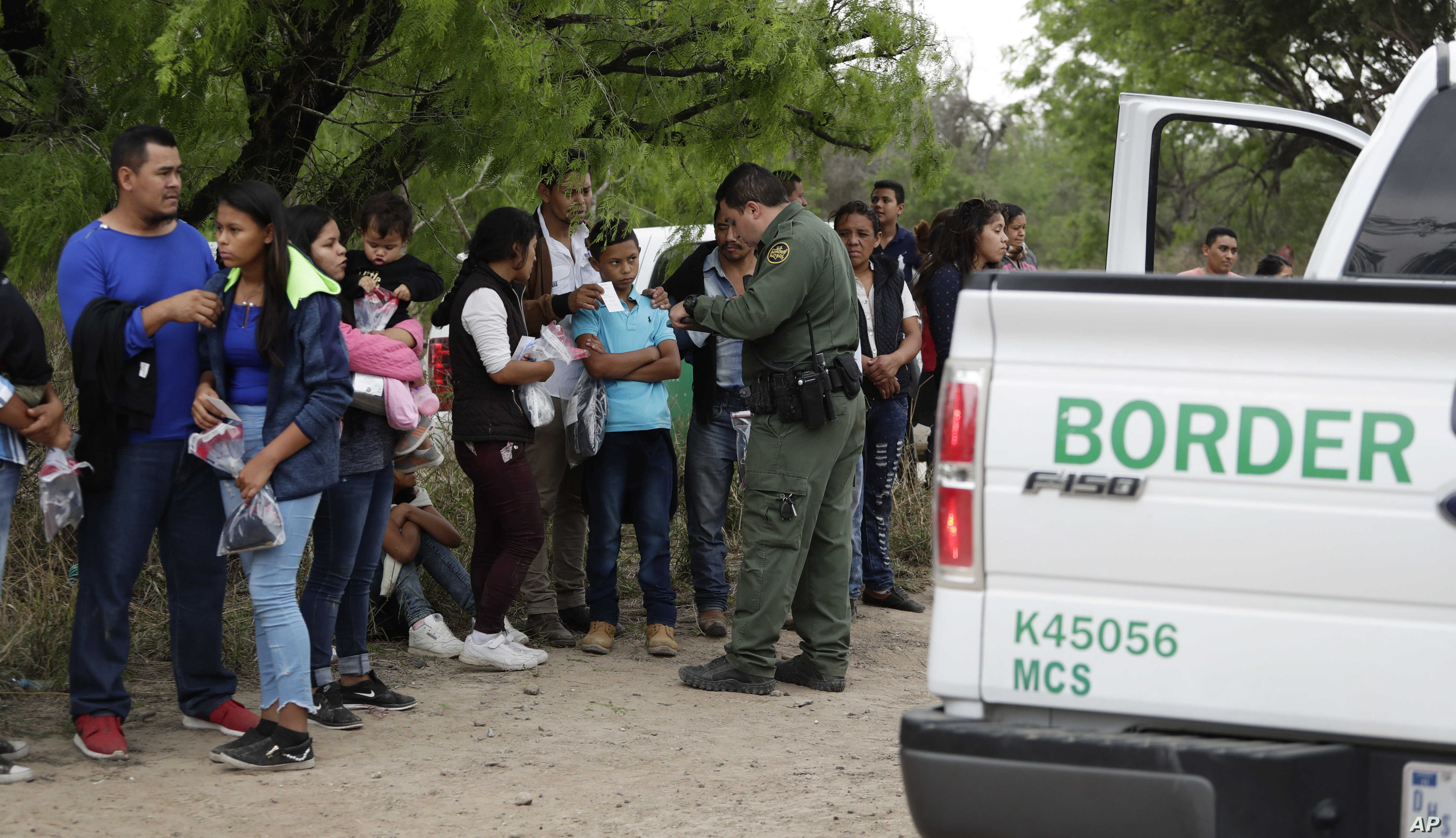 FILE - A U.S. Border Patrol agent checks the names and documents of families who crossed the nearby U.S.-Mexico border, near McAllen, Texas, March 14, 2019.