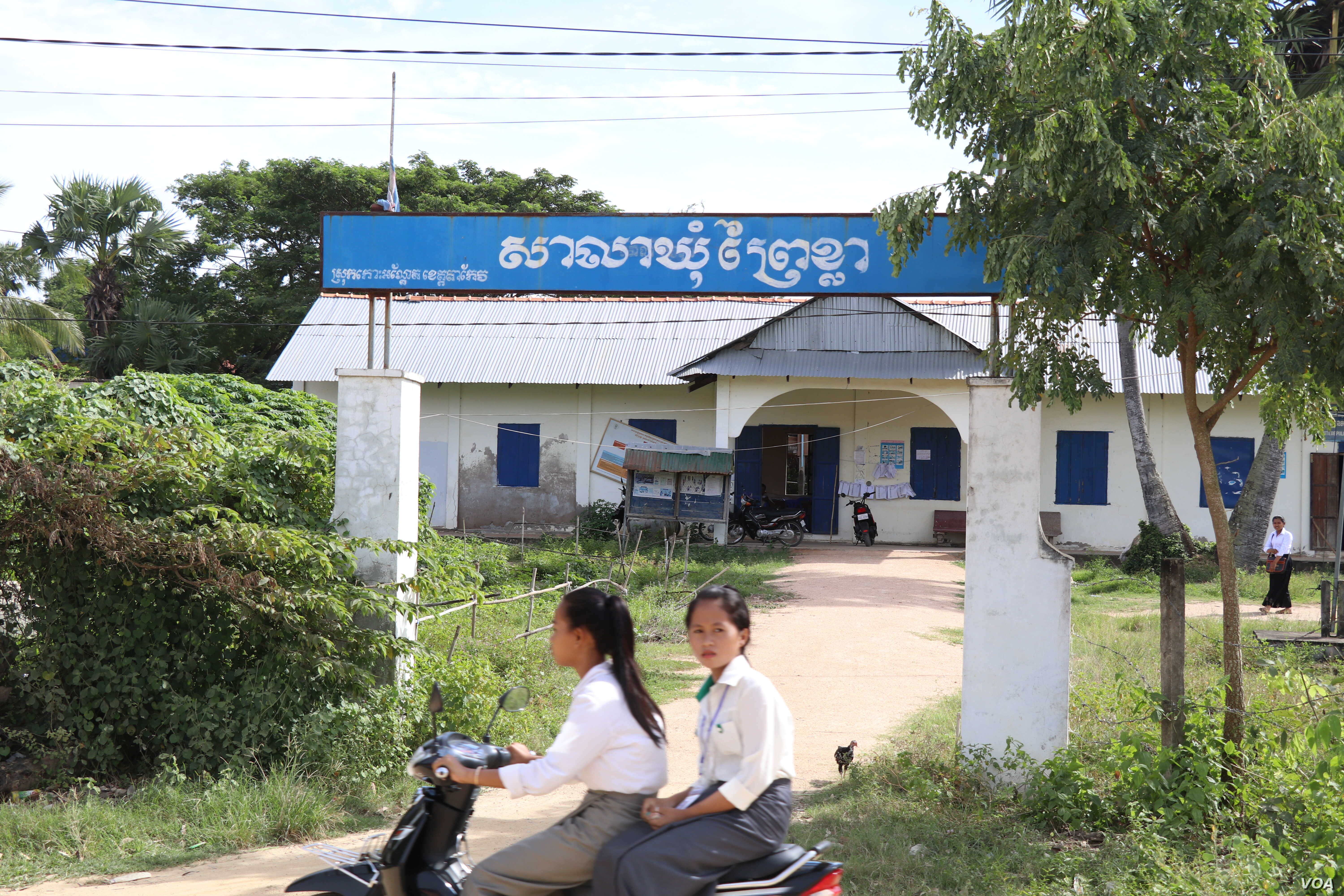 Students drive past the Prey Khla commune office in Takeo province, Nov. 27, 2017.
