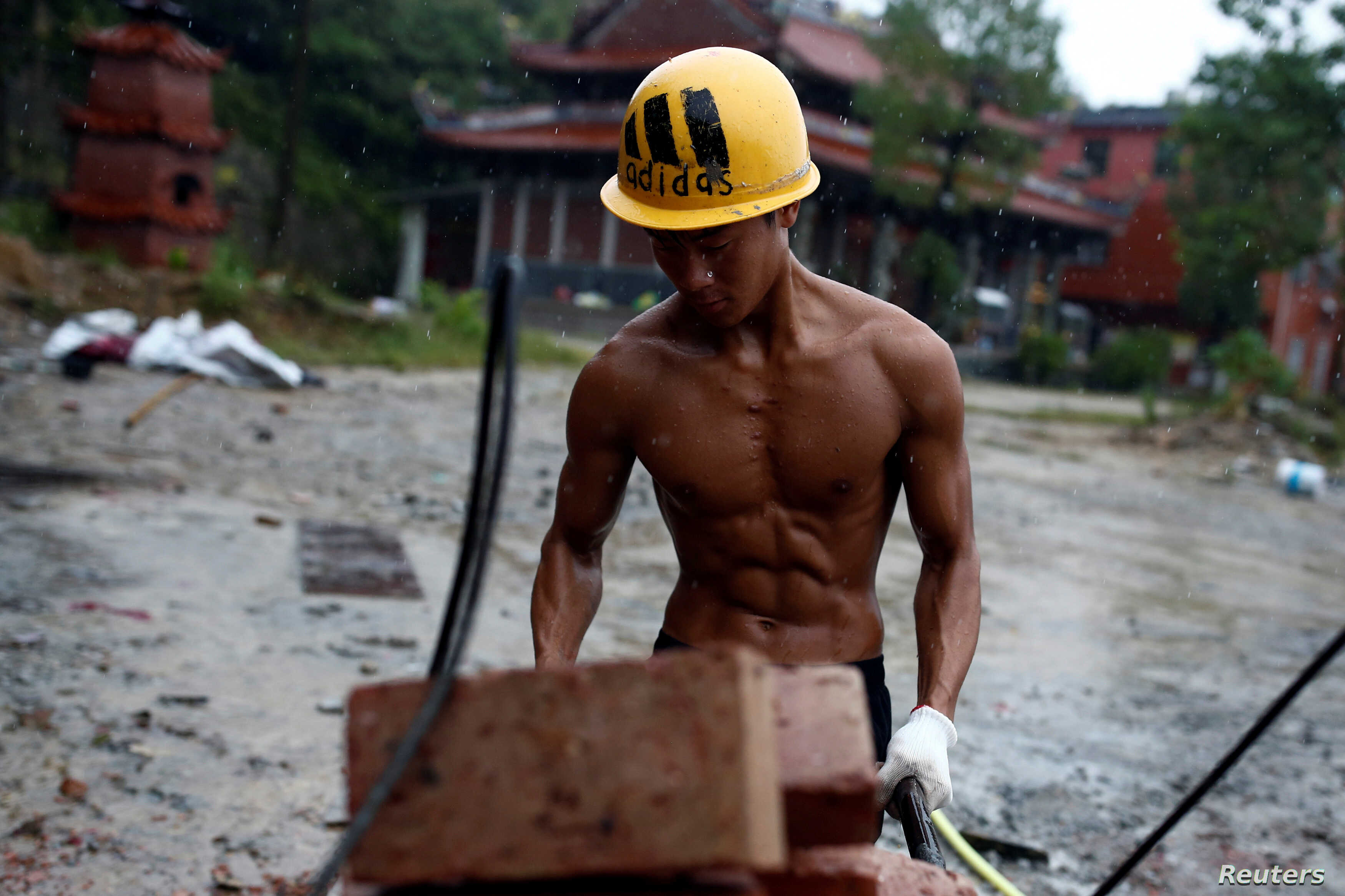 FILE - Shi Shenwei pulls a wheelbarrow at the construction site of a Buddhist temple in the village of Huangshan, in Fujian Province, China, on September 28, 2016.