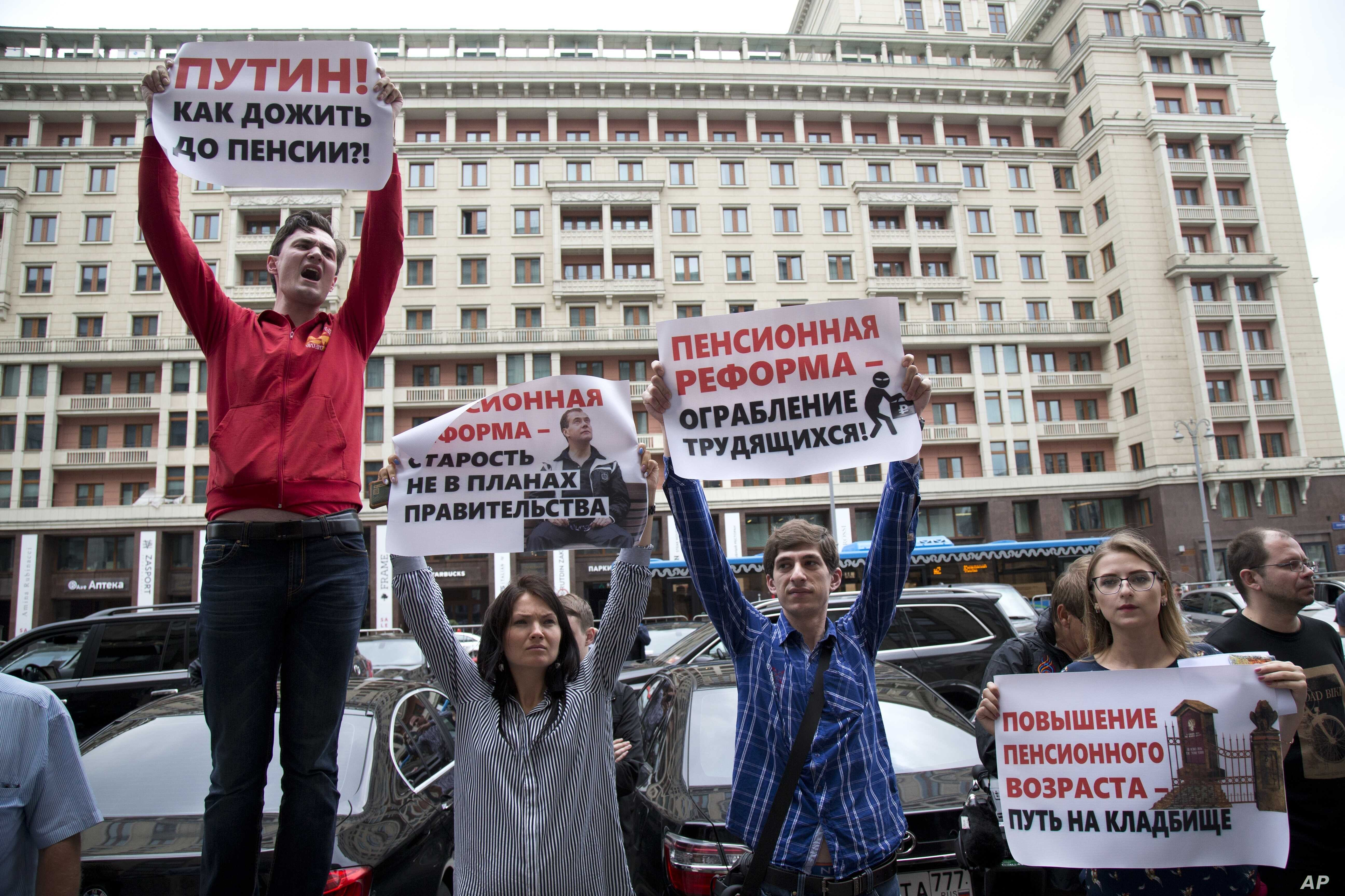 FILE - Russian hold placards during a protest against plans to raise the retirement age and reform the current pension system, in front of the Russian State Duma, the lower house of the Russian Parliament, in Moscow, Russia, July 19, 2018.