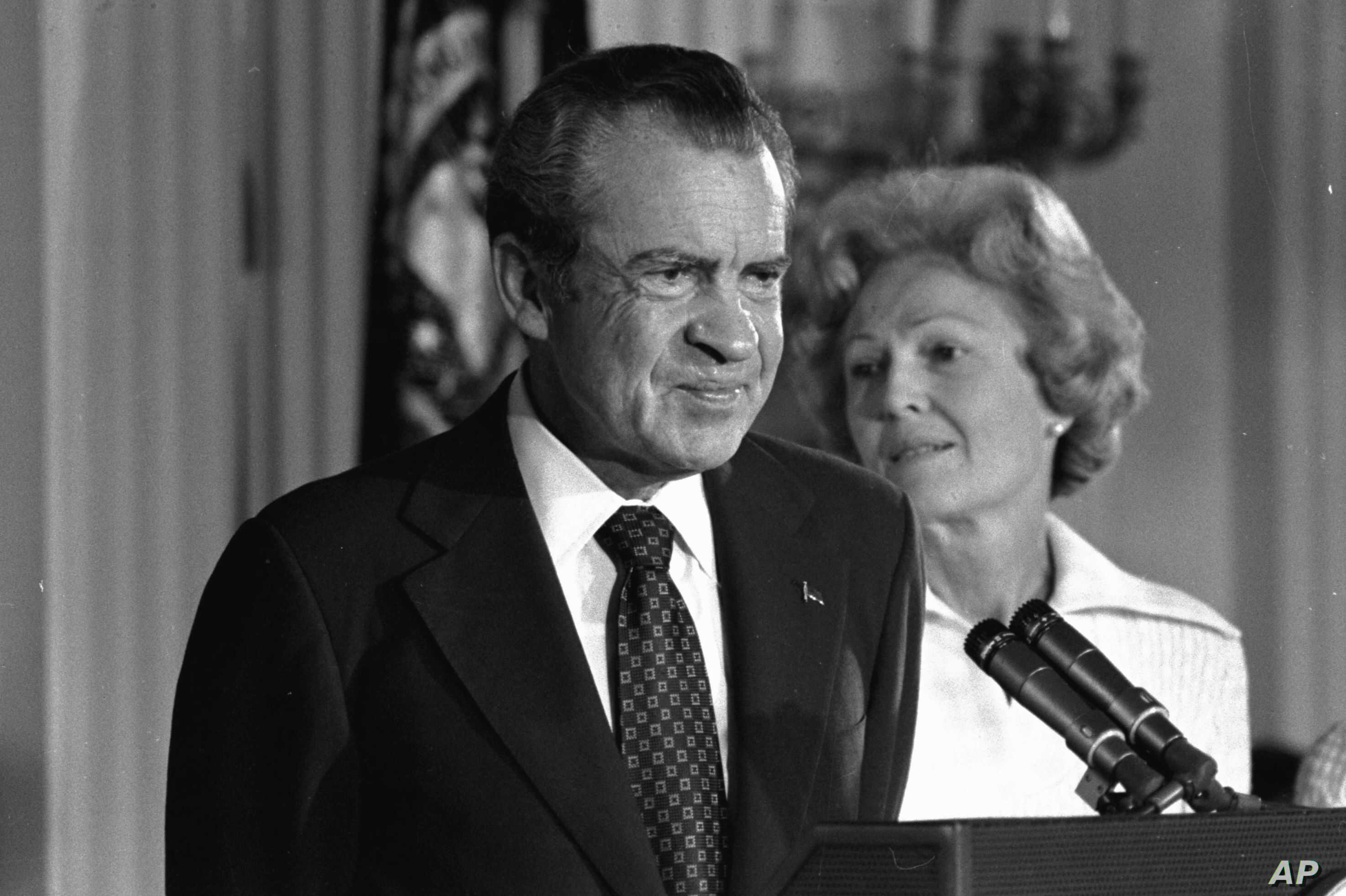 In this Aug. 9, 1974 black-and-white file photo, President Richard M. Nixon and his wife Pat Nixon are shown standing together in the East Room of the White House in Washington.
