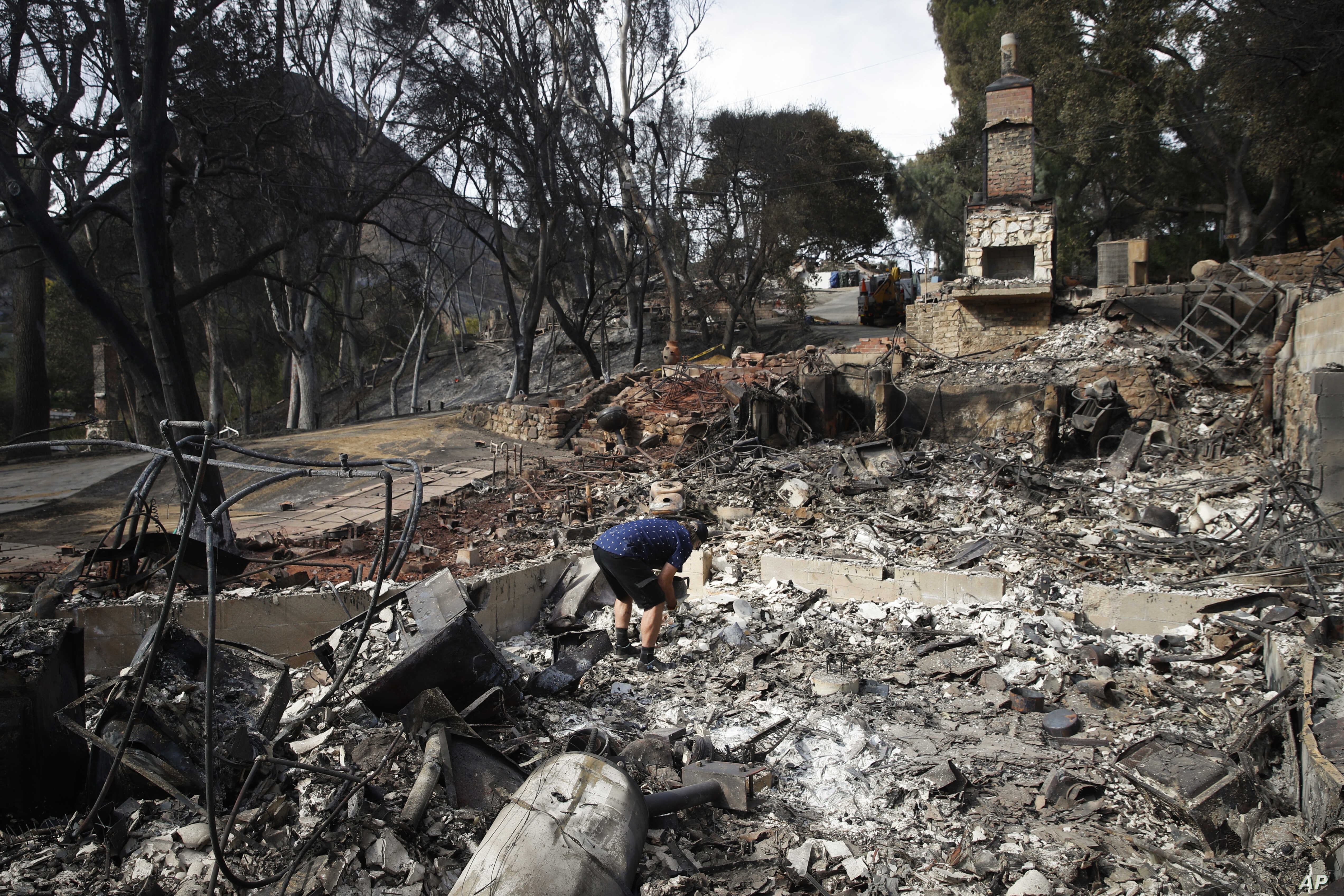 Roger Kelton searches through the remains of his mother-in-law's home leveled by the Woolsey Fire, Nov. 13, 2018, in the southern California city of Agoura Hills.