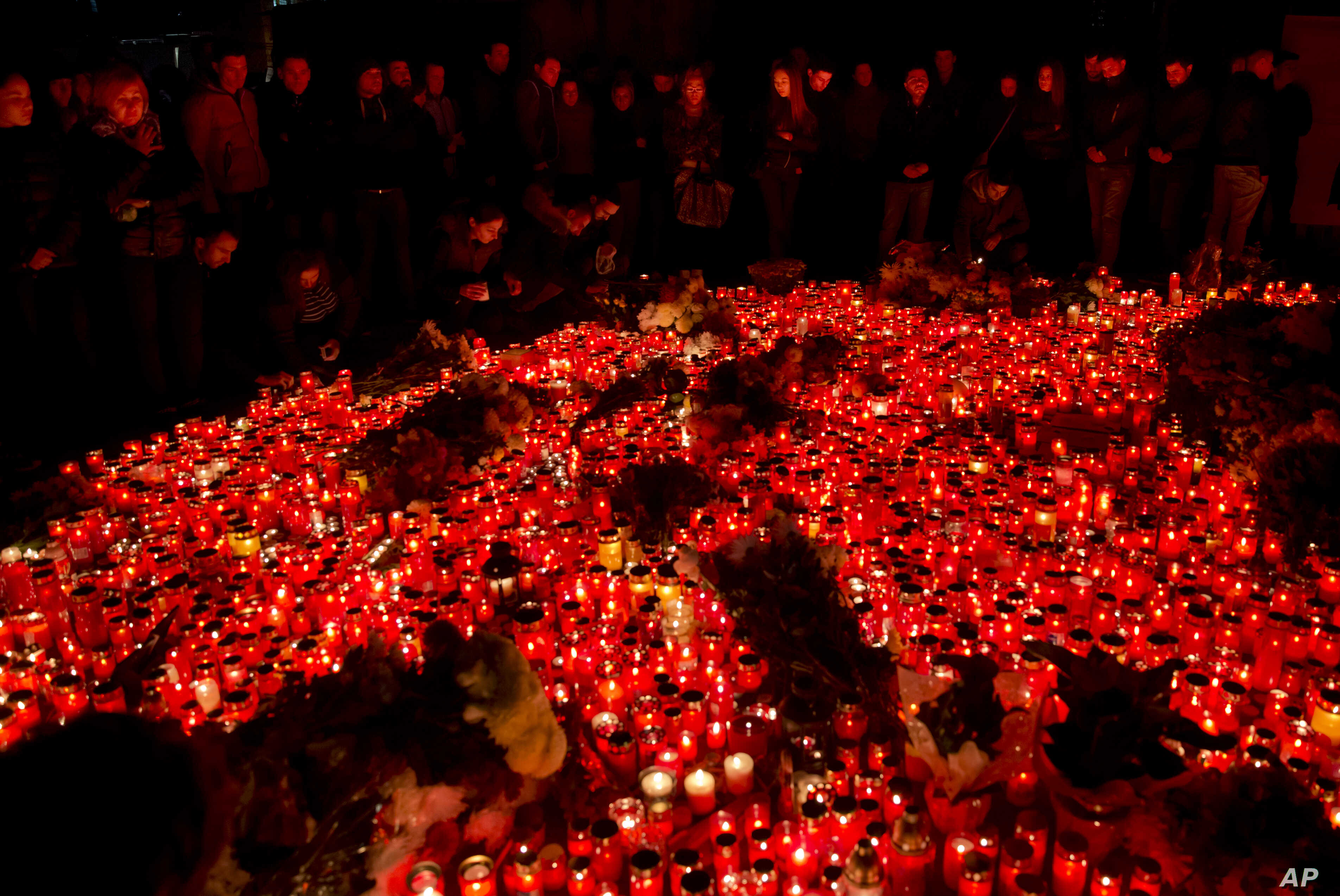 People, lit by burning candles, stand outside the compound that housed a nightclub where a fire occurred in the early Saturday in Bucharest, Romania, to pay respects to the victims, marking 24 hours after the accident, Nov. 1, 2015.