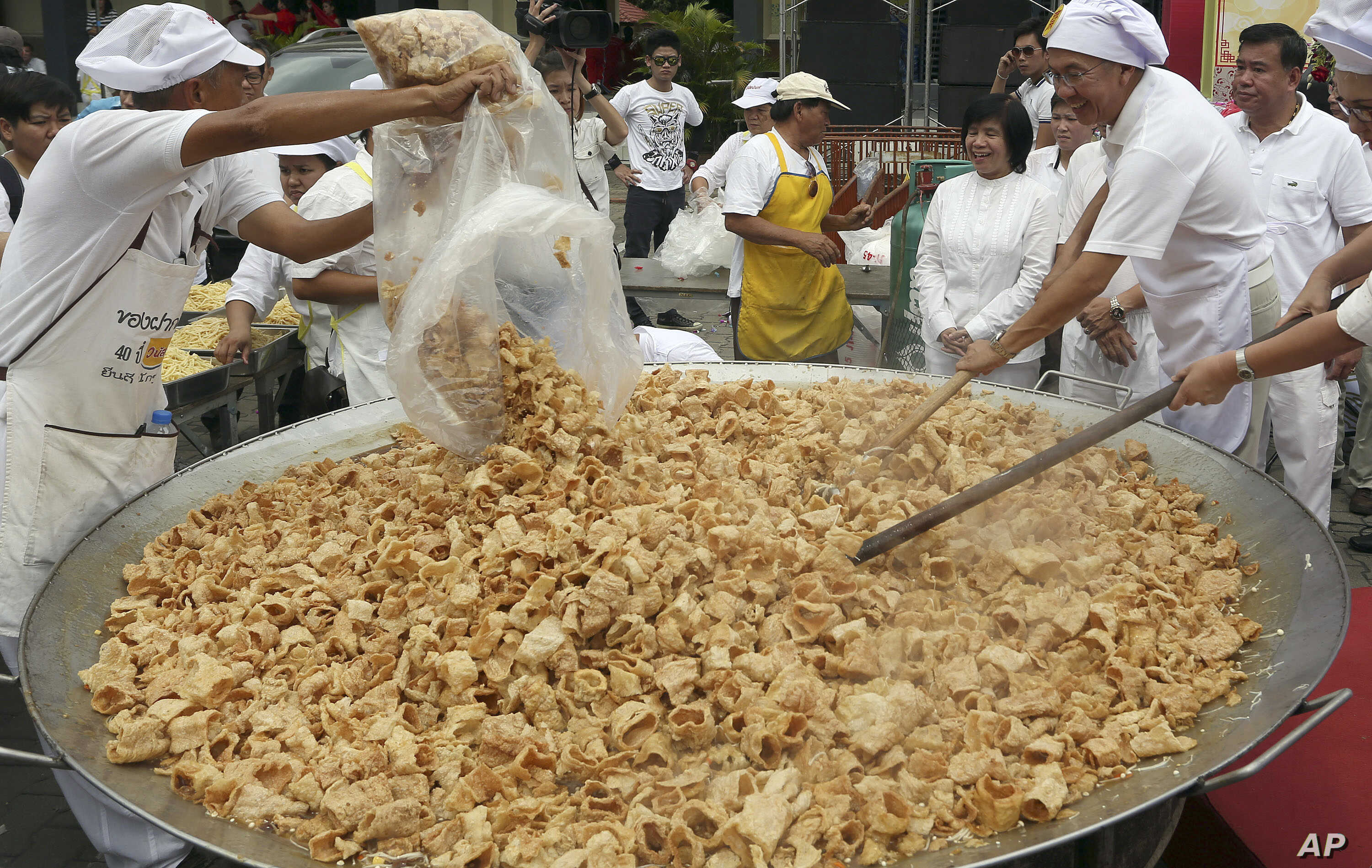 Thai chefs cook vegetarian food from a giant cooking bowl during the vegetarian festival celebration in Chiang Mai province, northern Thailand, Wednesday, Sept. 24, 2014.