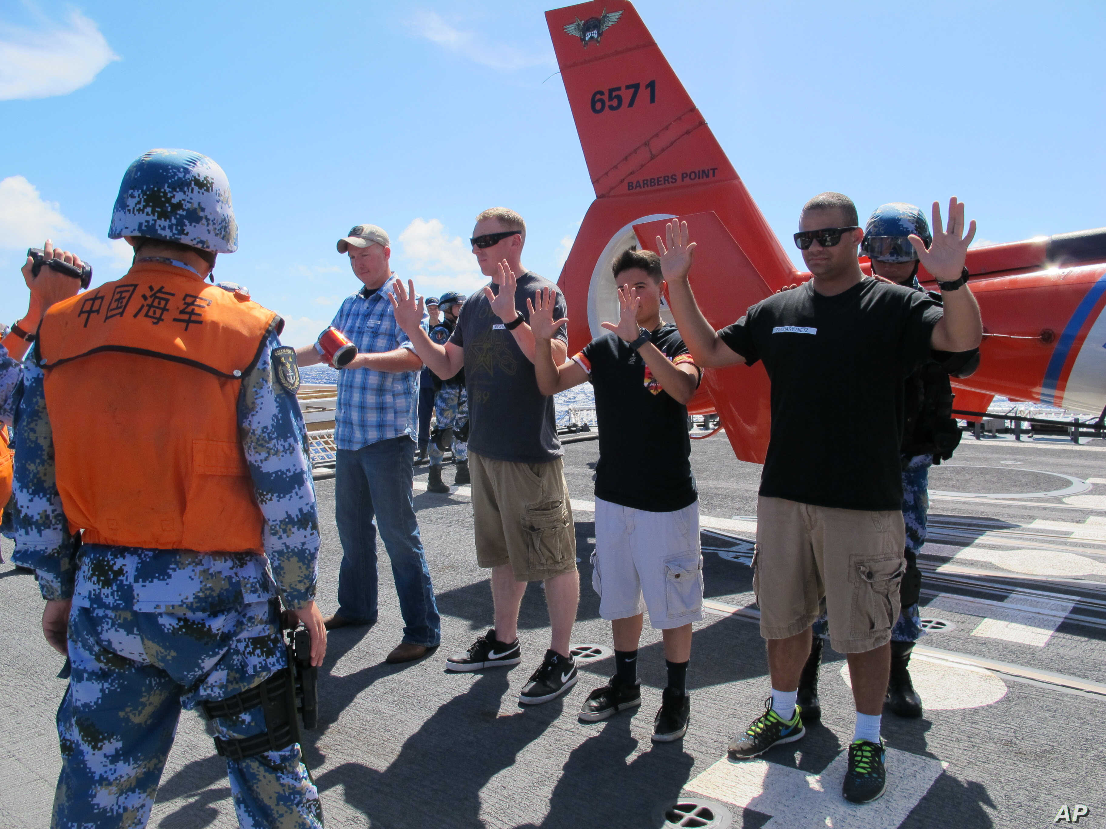 People's Liberation Army sailors pat down U.S. Coast Guardsmen playing the role of merchant mariners aboard the Coast Guard cutter Waesche off Hawaii, July 16, 2014. Chinese sailors boarded the Coast Guard cutter Waesche for a drill checking cargo as...