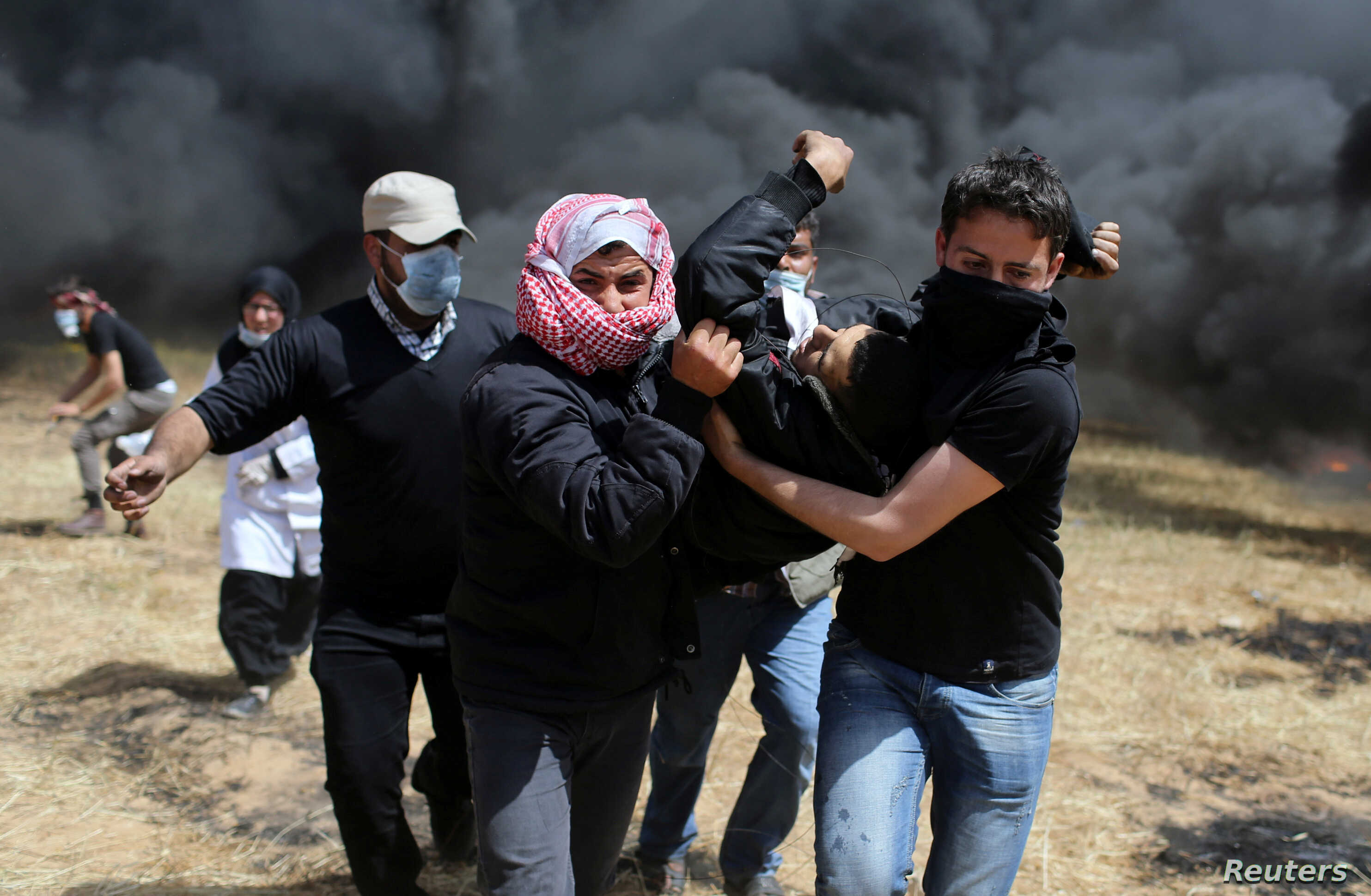 A wounded Palestinian demonstrator is evacuated during clashes with Israeli troops at the Israel-Gaza border at a protest demanding the right to return to their homeland, in the southern Gaza Strip, April 6, 2018.