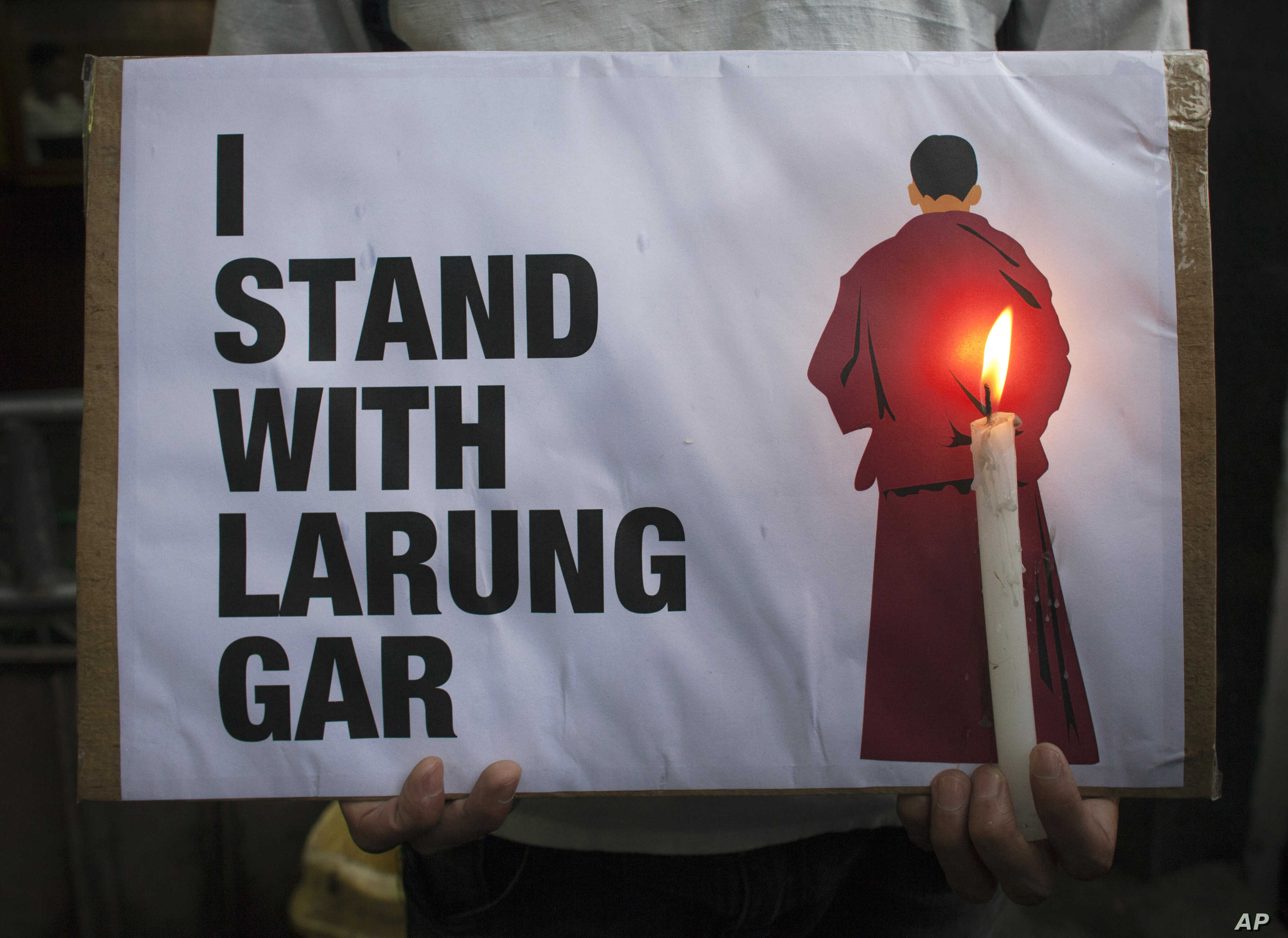 An exiled Tibetan holds a placard as he participates in a protest against the demolition of buildings in Larung Gar by Chinese authorities, during a demonstration in Dharmsala, India, Aug. 10, 2016.