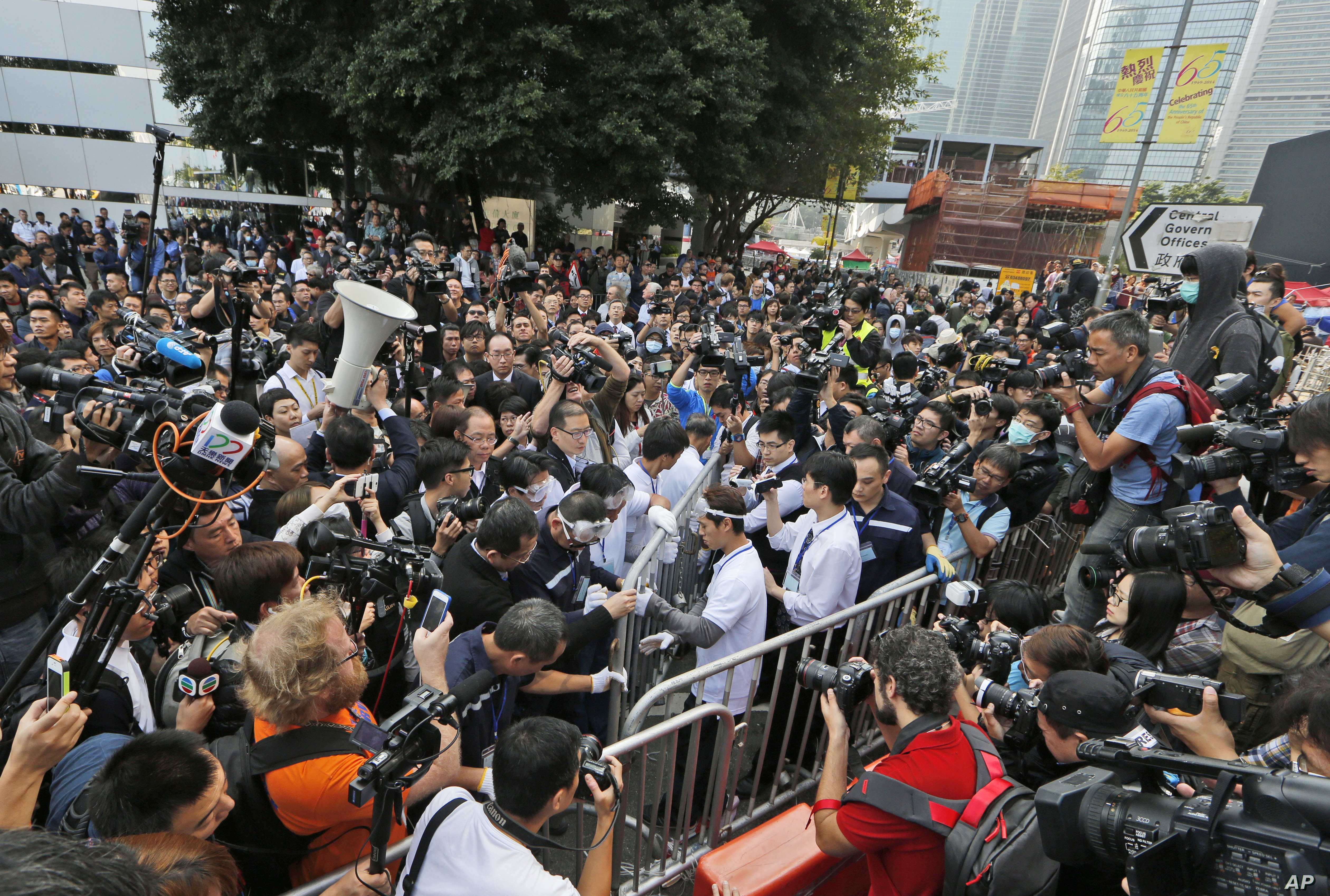 Workers, center, start clearing away barricades at an occupied area outside government headquarters in Hong Kong, Nov. 18, 2014.