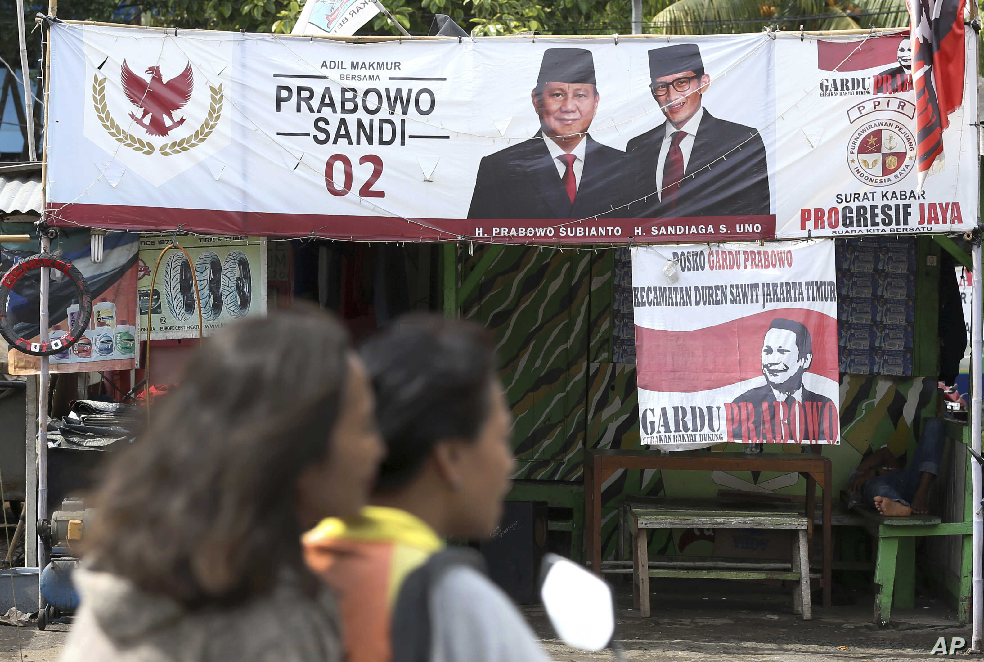 A couple rides a motorcycle past a campaign banners for Indonesian presidential candidate Prabowo Subianto, left, and his running mate Sandiaga Uno in Jakarta, Indonesia, Thursday, Jan. 17, 2019.