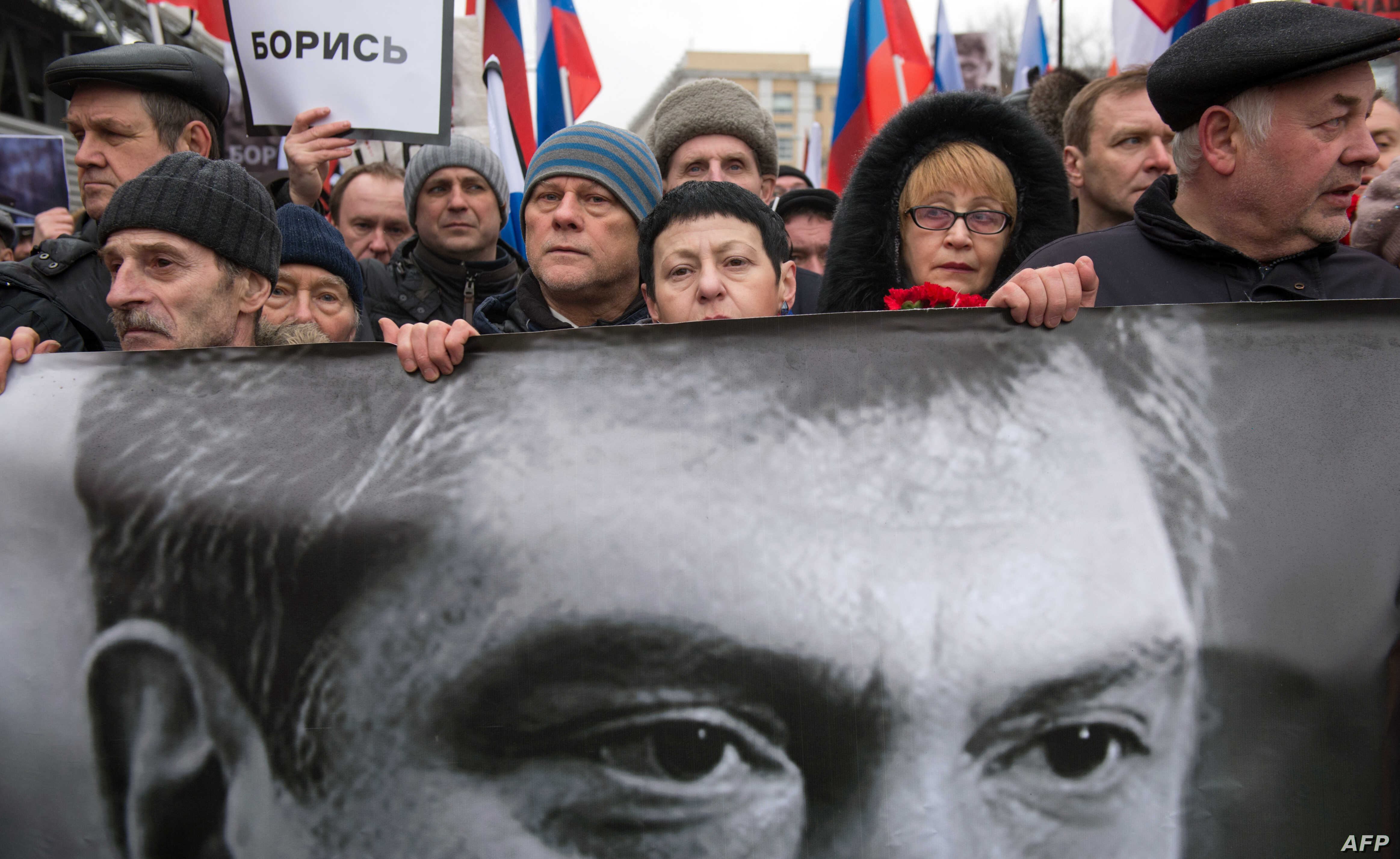 FILE - Russia's opposition supporters carrying a banner bearing a portrait of Kremlin critic Boris Nemtsov during a march in central Moscow, March 1, 2015.