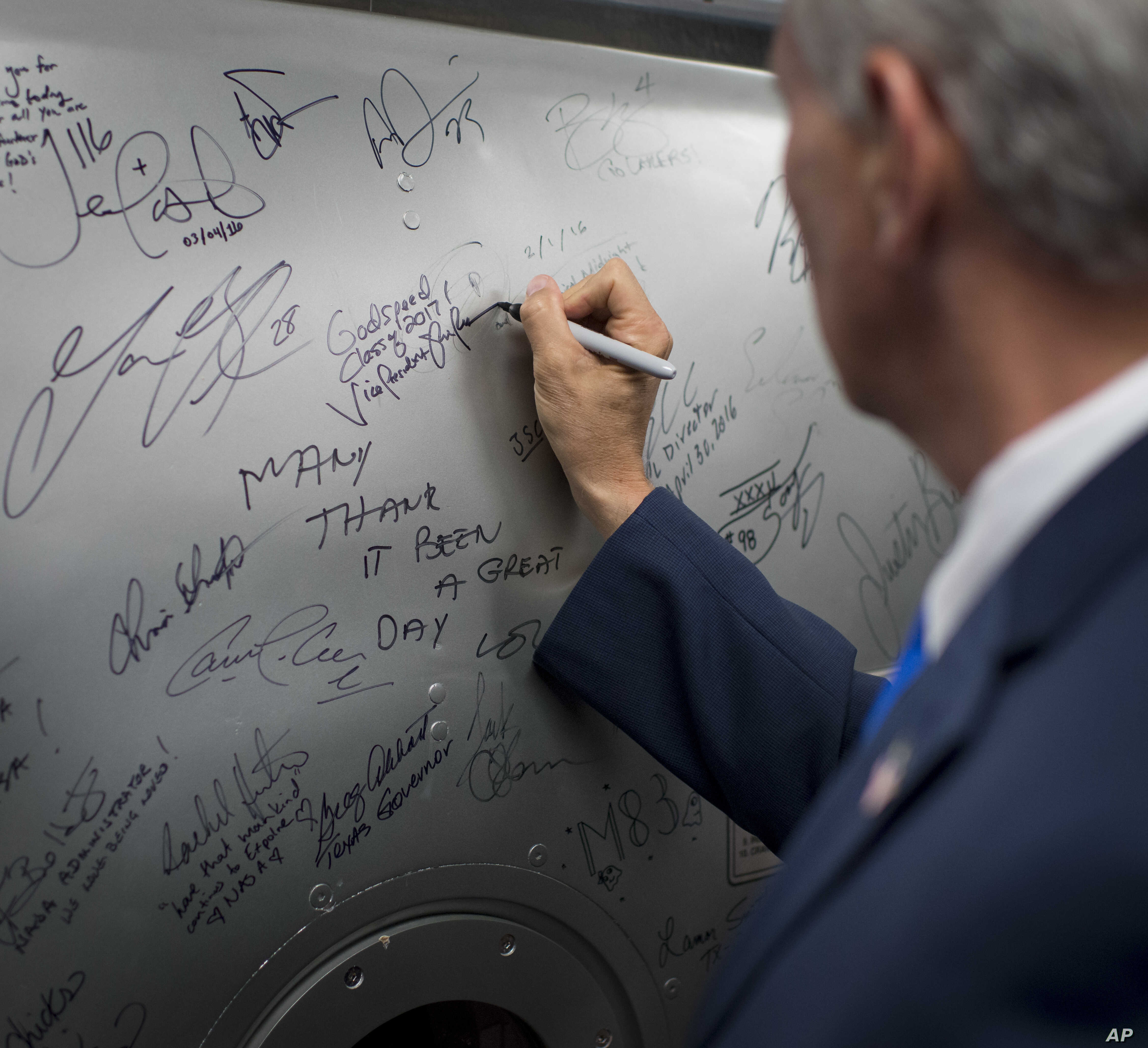 In the tradition of others, Vice President Mike Pence signs a hatch from a space station training module mockup, June 7, 2017, at NASA's Johnson Space Center in Houston, Texas.