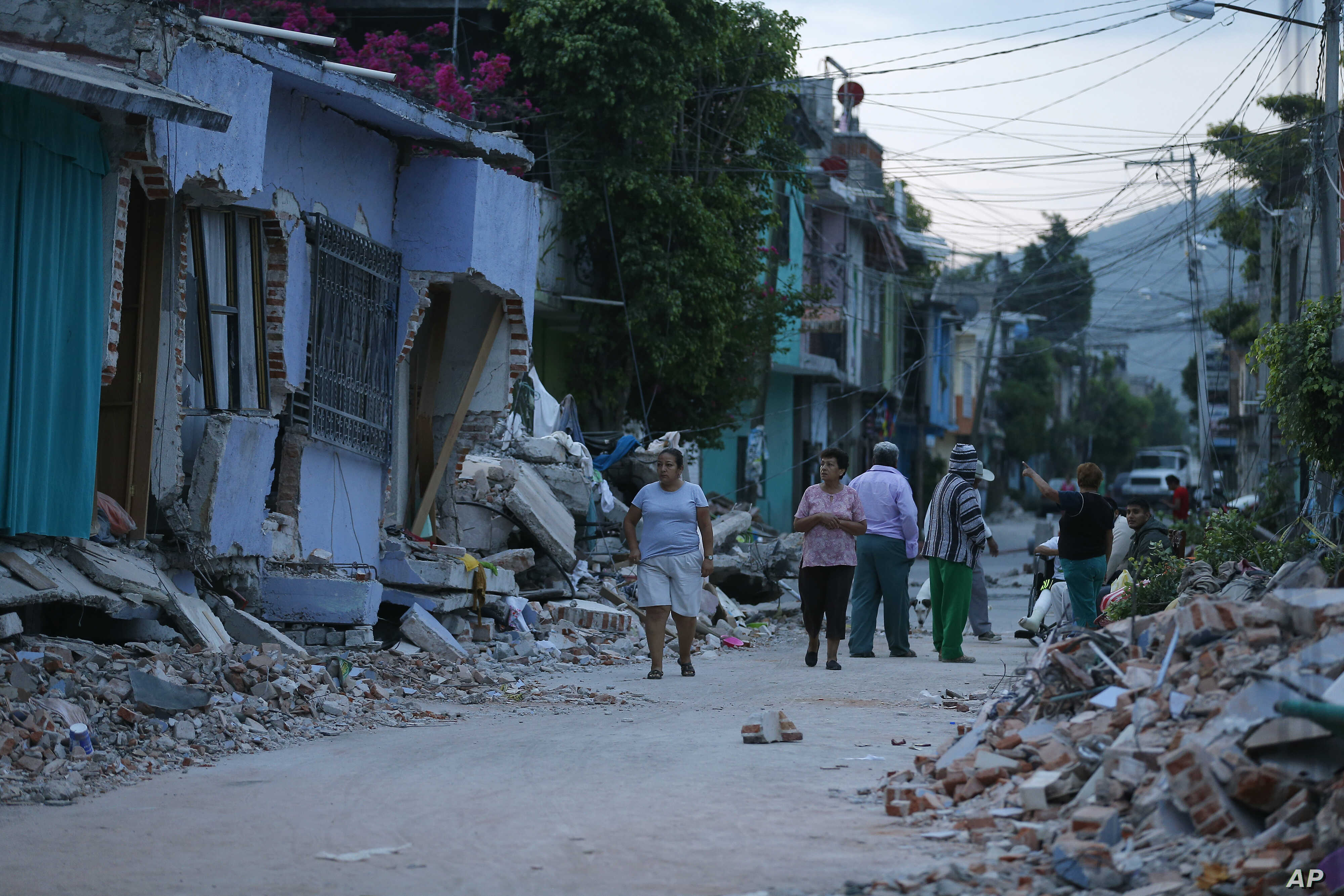 Residents stand next to buildings damaged by a 7.1 earthquake, in Jojutla, Morelos state, Mexico, Sept. 20, 2017.