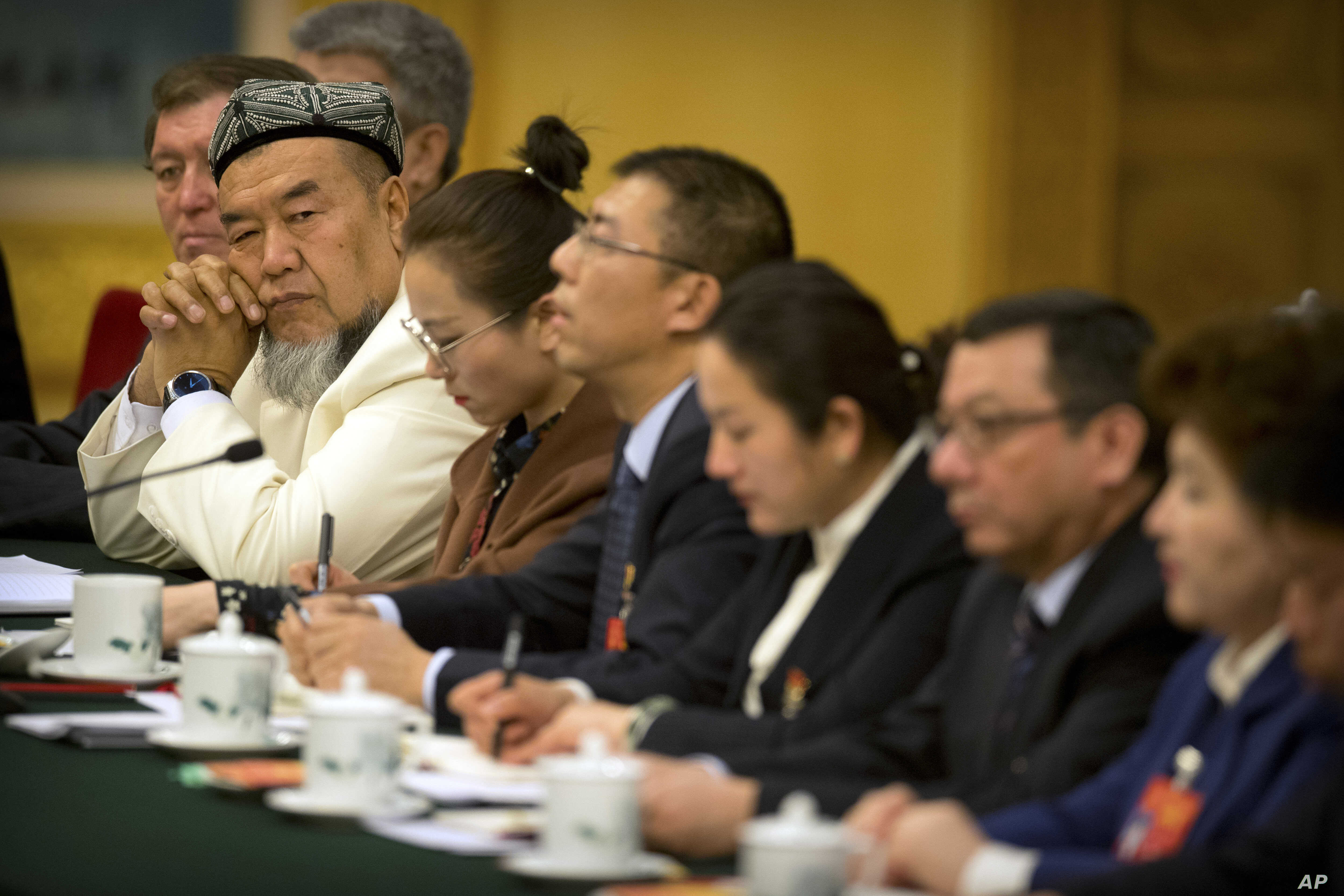 A delegate in traditional Uighur dress listens to a speaker during a group discussion meeting with delegates from China's Xinjiang Uighur Autonomous Region on the sidelines of China's National People's Congress (NPC) at the Great Hall of the People i...