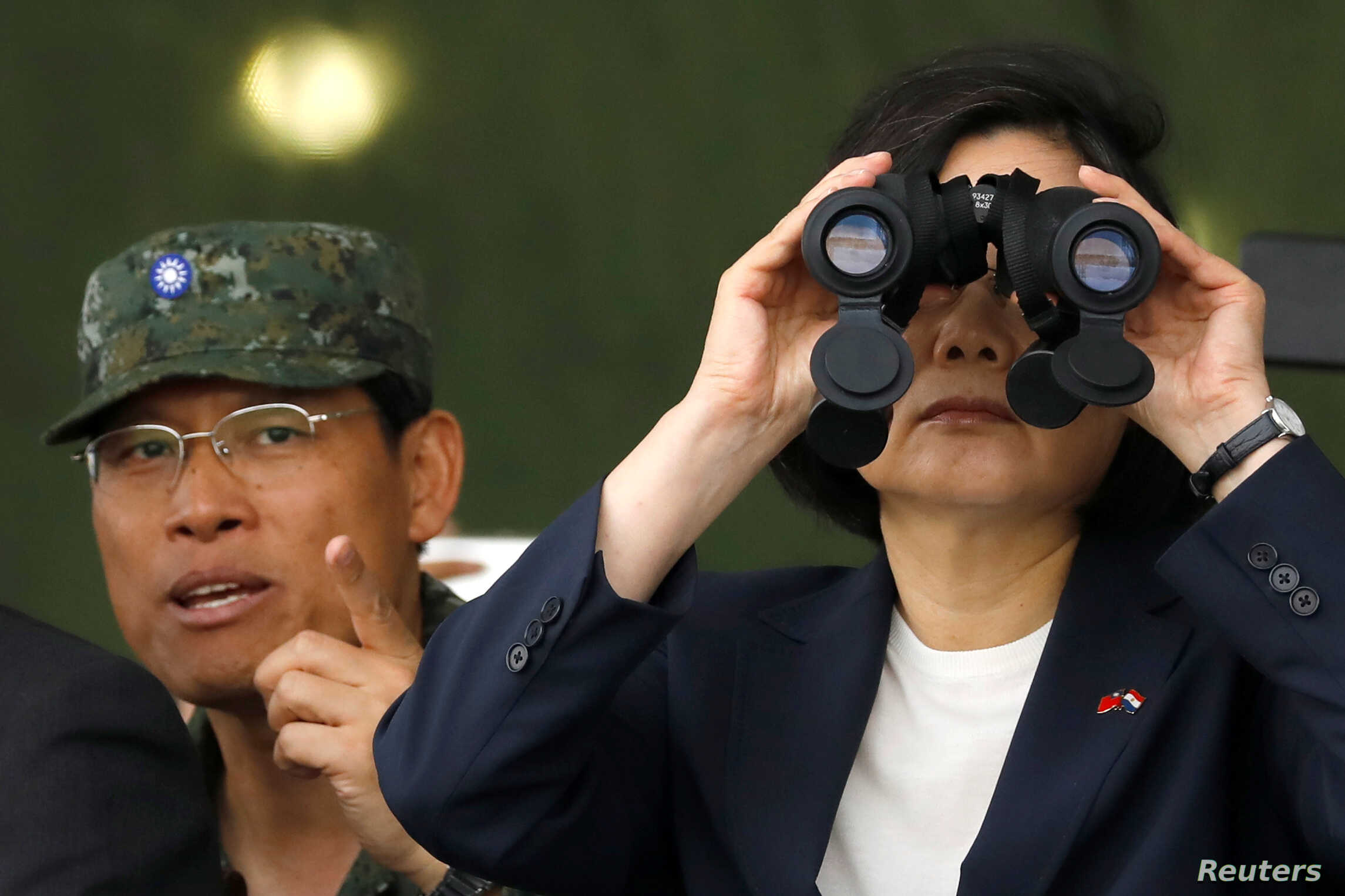Taiwan's President Tsai Ing-wen looks through a pair of binoculars during anti-invasion drill, simulating the China's People's Liberation Army invading the island, in Taoyuan, Taiwan, Oct. 9, 2018.