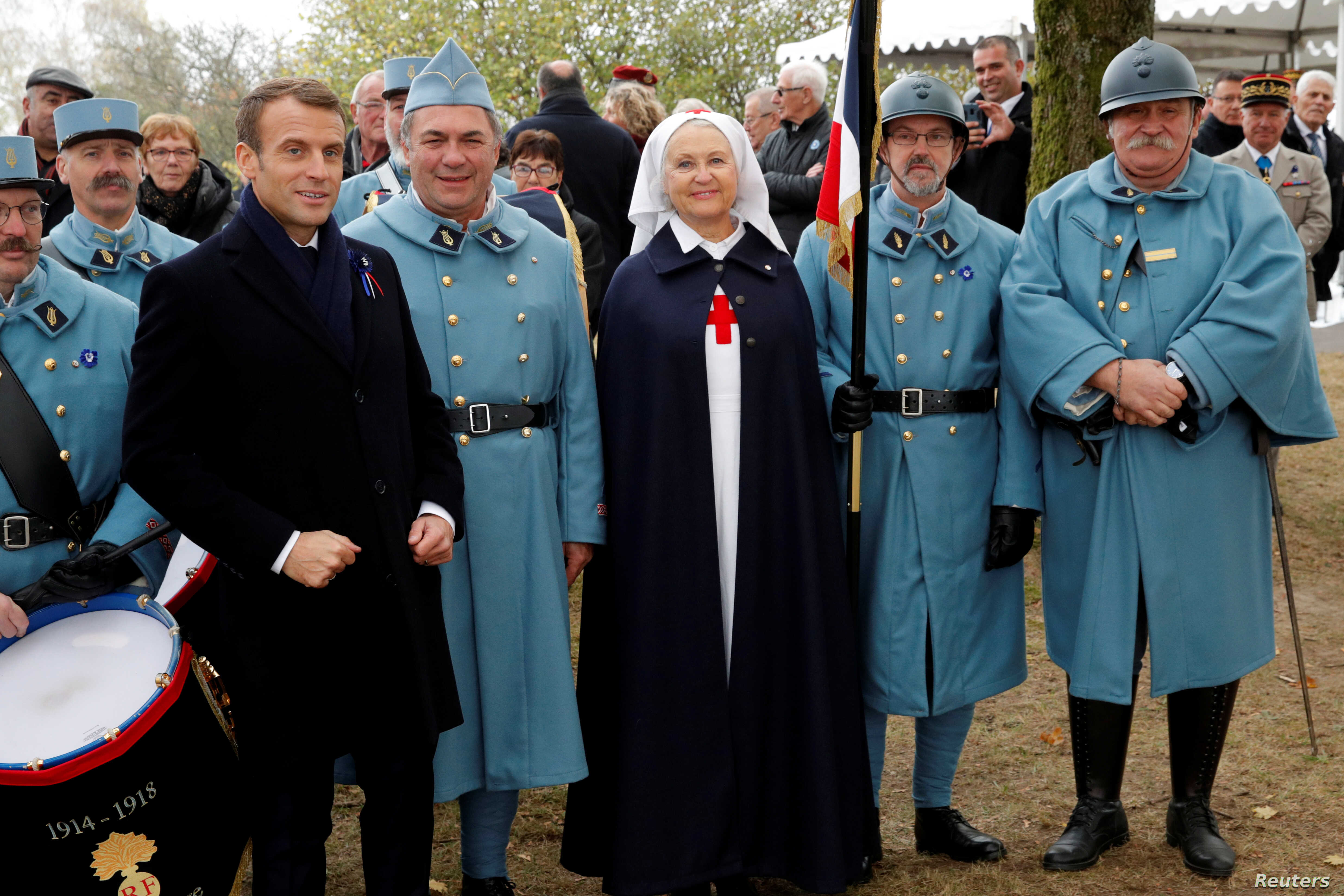 French President Emmanuel Macron poses with history enthusiasts, dressed with vintage army uniforms as Poilu (French soldier in World War I), after a ceremony at the Memorial to the Battle of Morhange, Eastern France, Nov.  5, 2018 as part of a World...