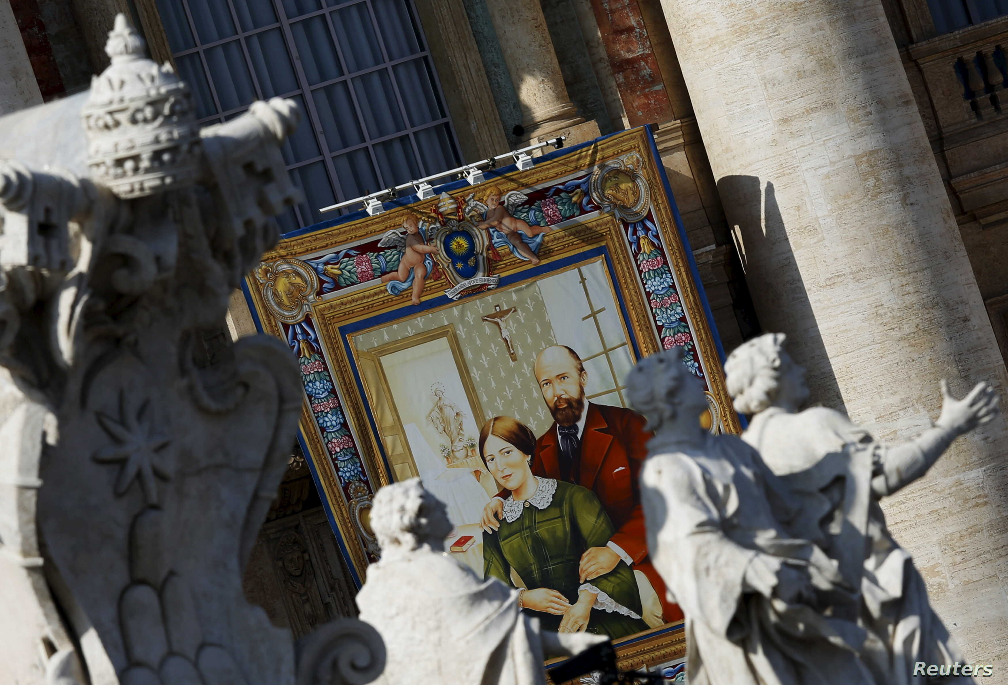 A tapestry showing Louis and Zelie Martin, parents of St. Therese of Lisieux, hangs from a balcony as Pope Francis leads the mass for their canonization in Saint Peter's Square at the Vatican, Oct. 18, 2015.