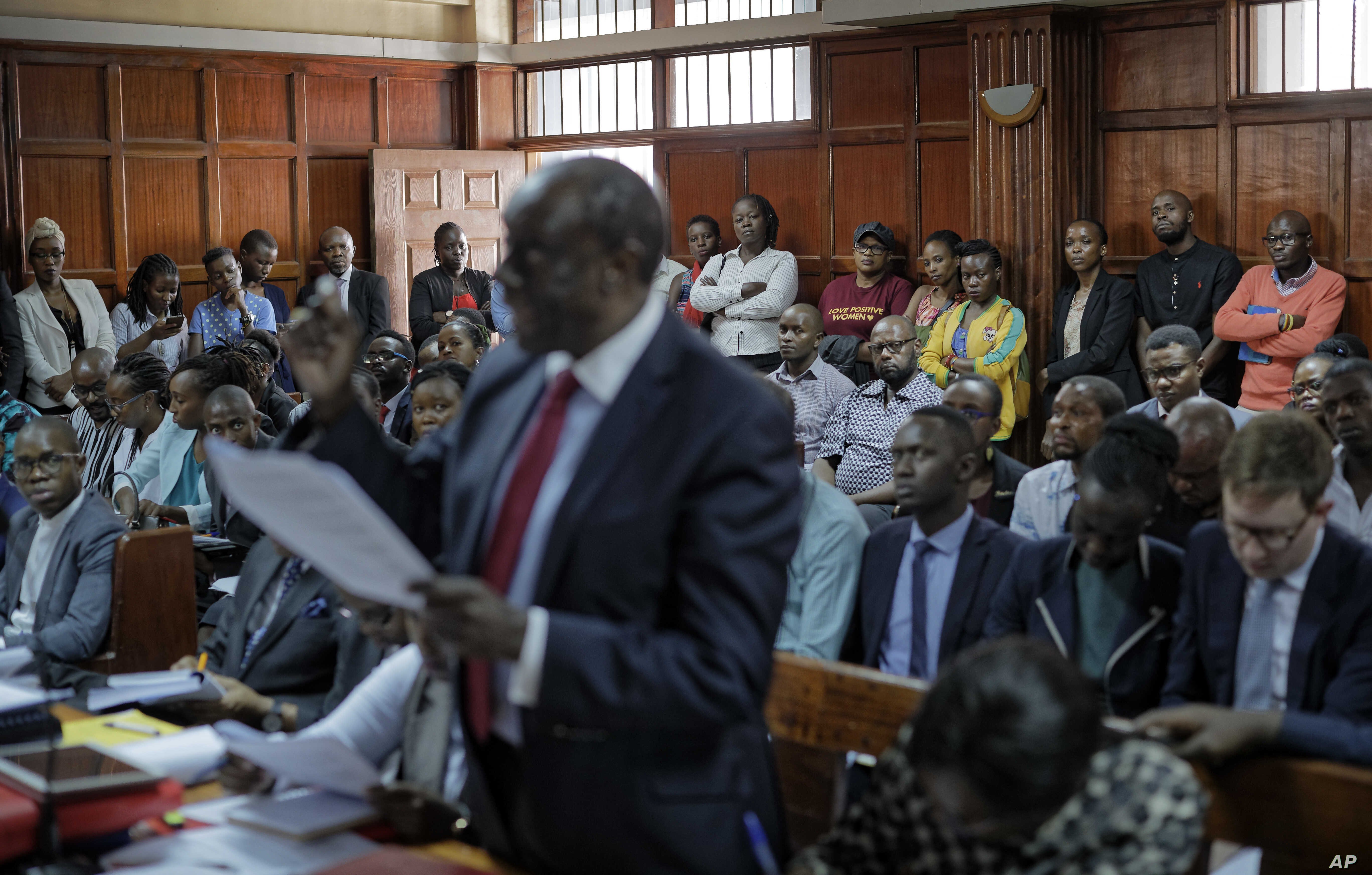 Members of the public listen as the High Court in Kenya begins hearing arguments in a case challenging parts of the penal code seen as targeting the lesbian, gay, bisexual and transgender communities, at the High Court in Nairobi, Kenya, Feb. 22, 201...