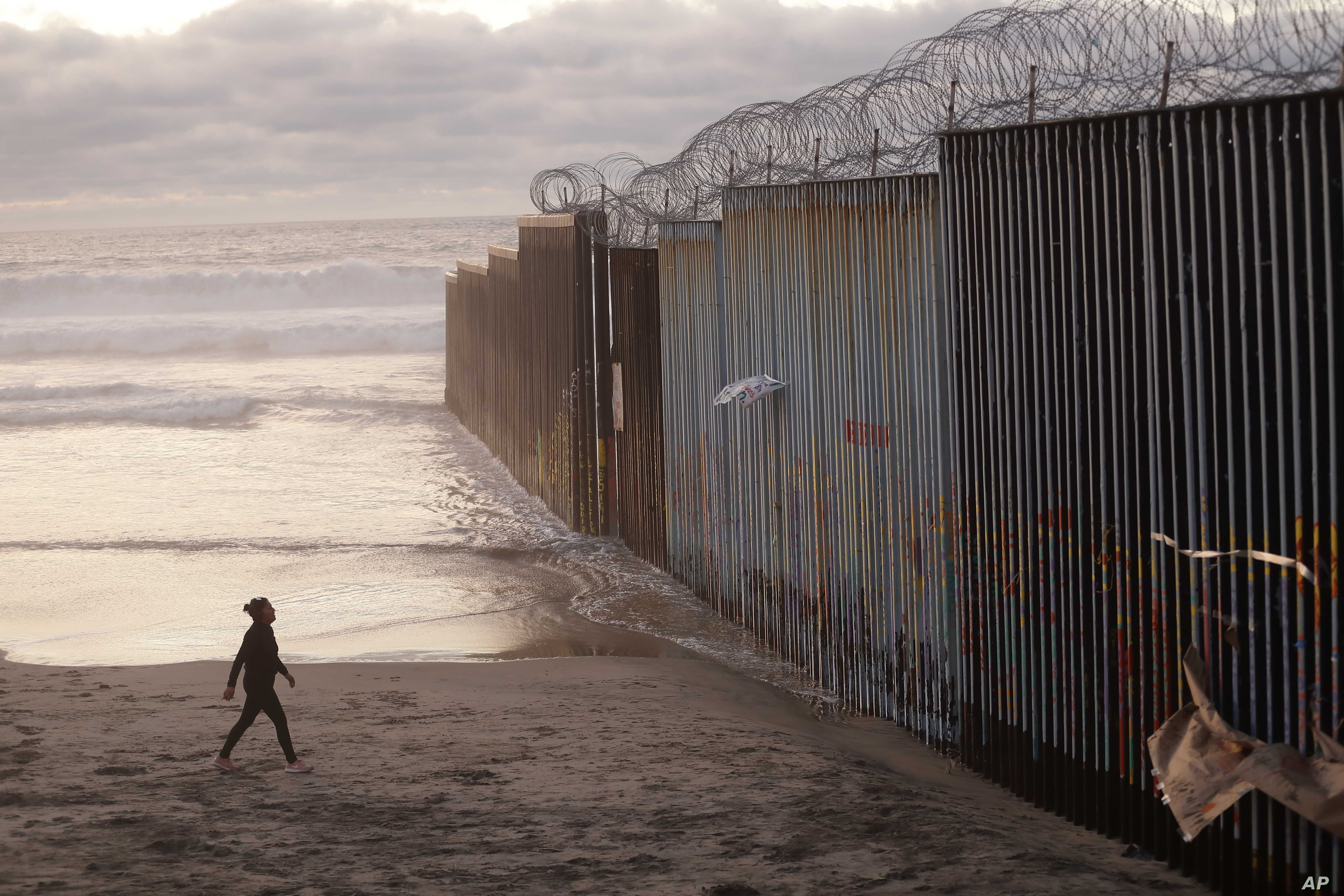 A woman walks on the beach, Jan. 9, 2019, next to the border wall topped with razor wire in Tijuana, Mexico.