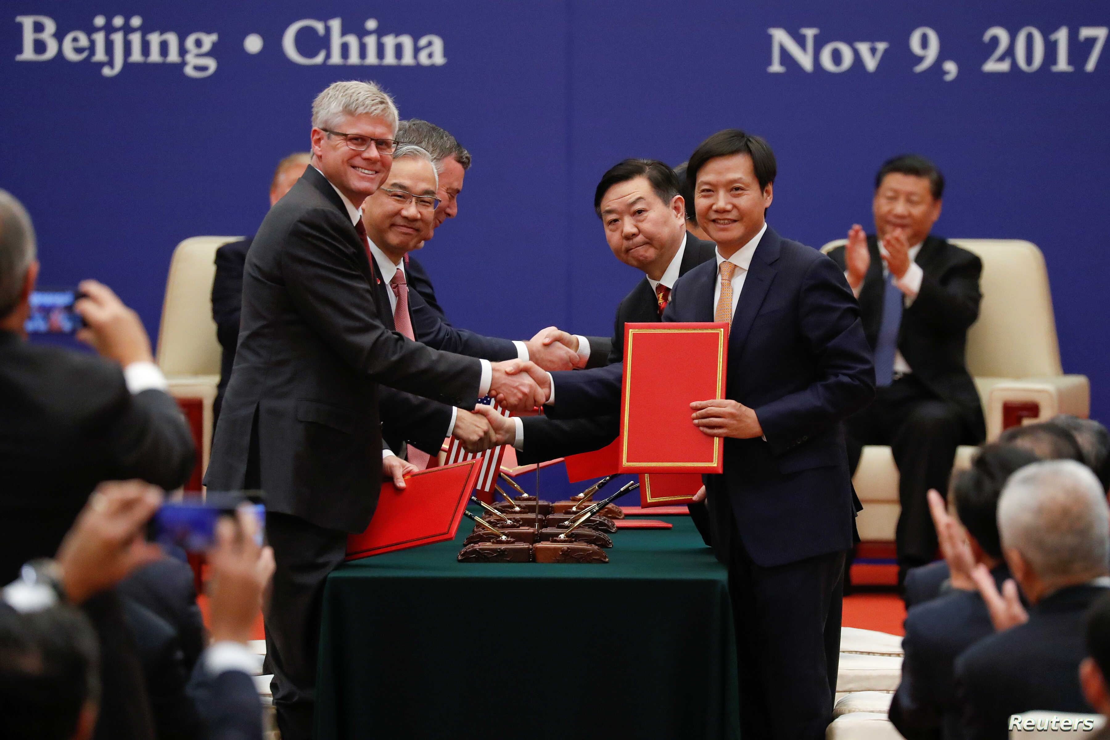 Business leaders shake hands during signing ceremony attended by U.S. President Donald Trump and China's President Xi Jinping at the Great Hall of the People in Beijing, Nov. 9, 2017.