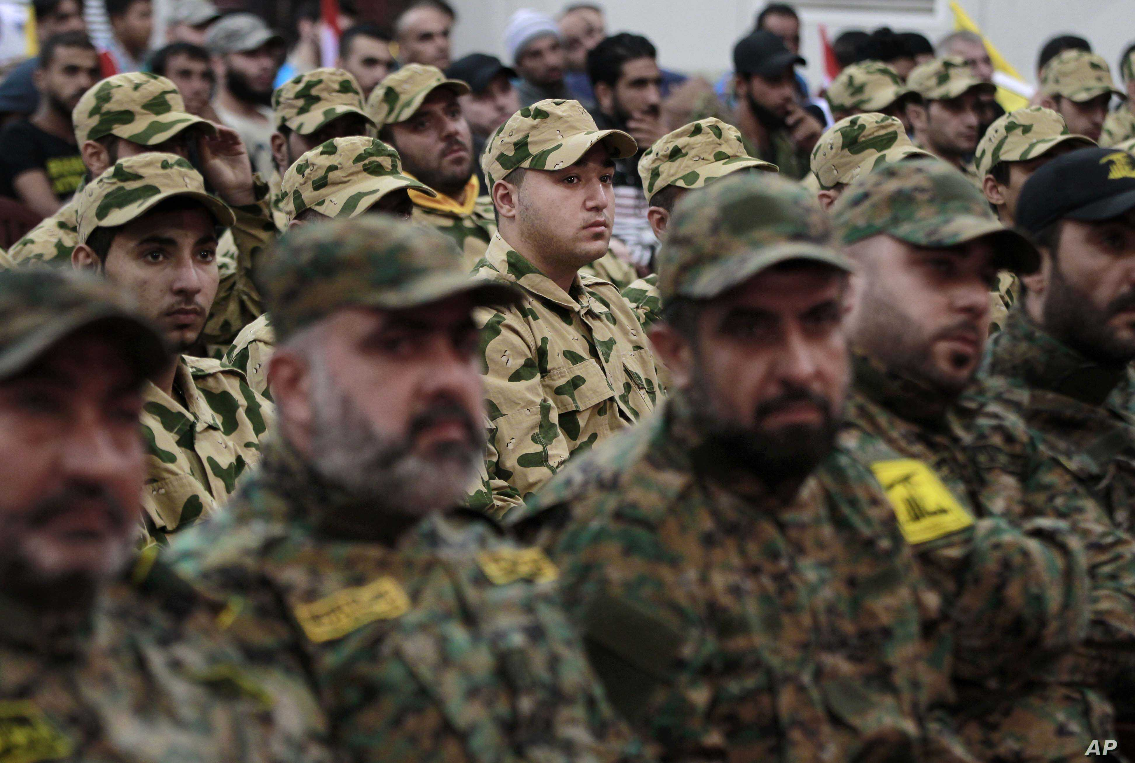 FILE - Hezbollah fighters listen to Hezbollah leader Sheik Hassan Nasrallah, as he speaks via a video link during a rally to mark the Hezbollah martyr day, in the southern suburb of Beirut, Lebanon.