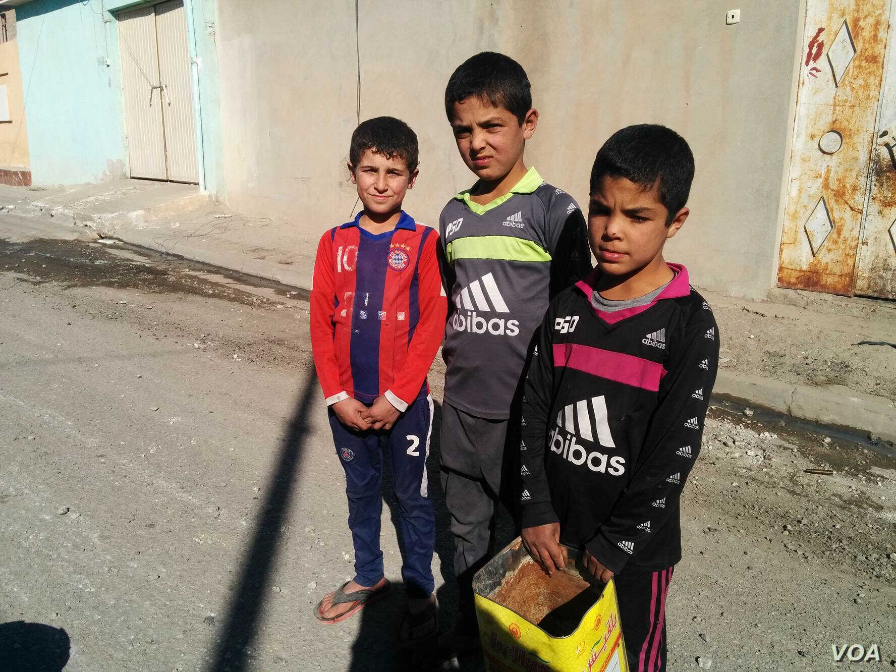 """""""We are scared, but we are used to it a little,"""" says Fahel, 12, (L) on his way to find food for his family's cow despite the ongoing gunfire and mortars on Nov. 19, 2016 in Mosul, Iraq."""