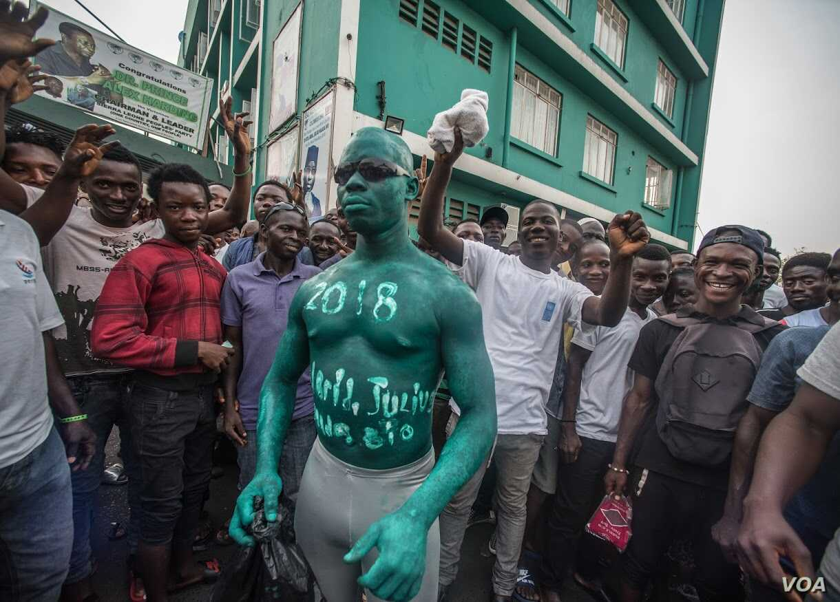A man has '2018, Julius Maada Bio' painted on his body in green, the color of SLPP outside SLPP headquarters, Sierra Leone. (O. Acland for VOA)