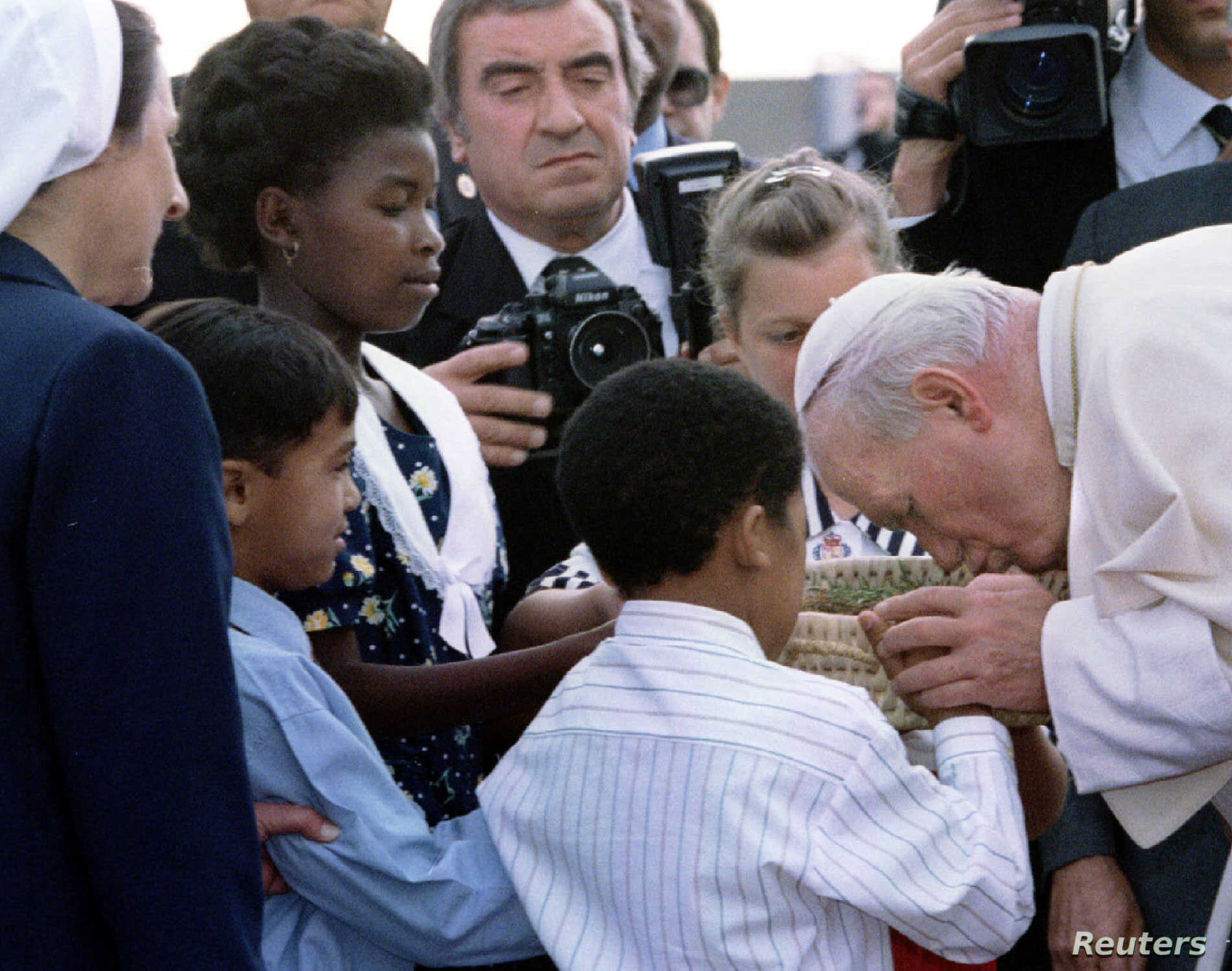 Pope John Paul II kisses a basket of South African soil presented to him by four children of different races as he arrives at Johannesburg International Airport, Sept. 16, 1995, at the start of his first official visit to the country.