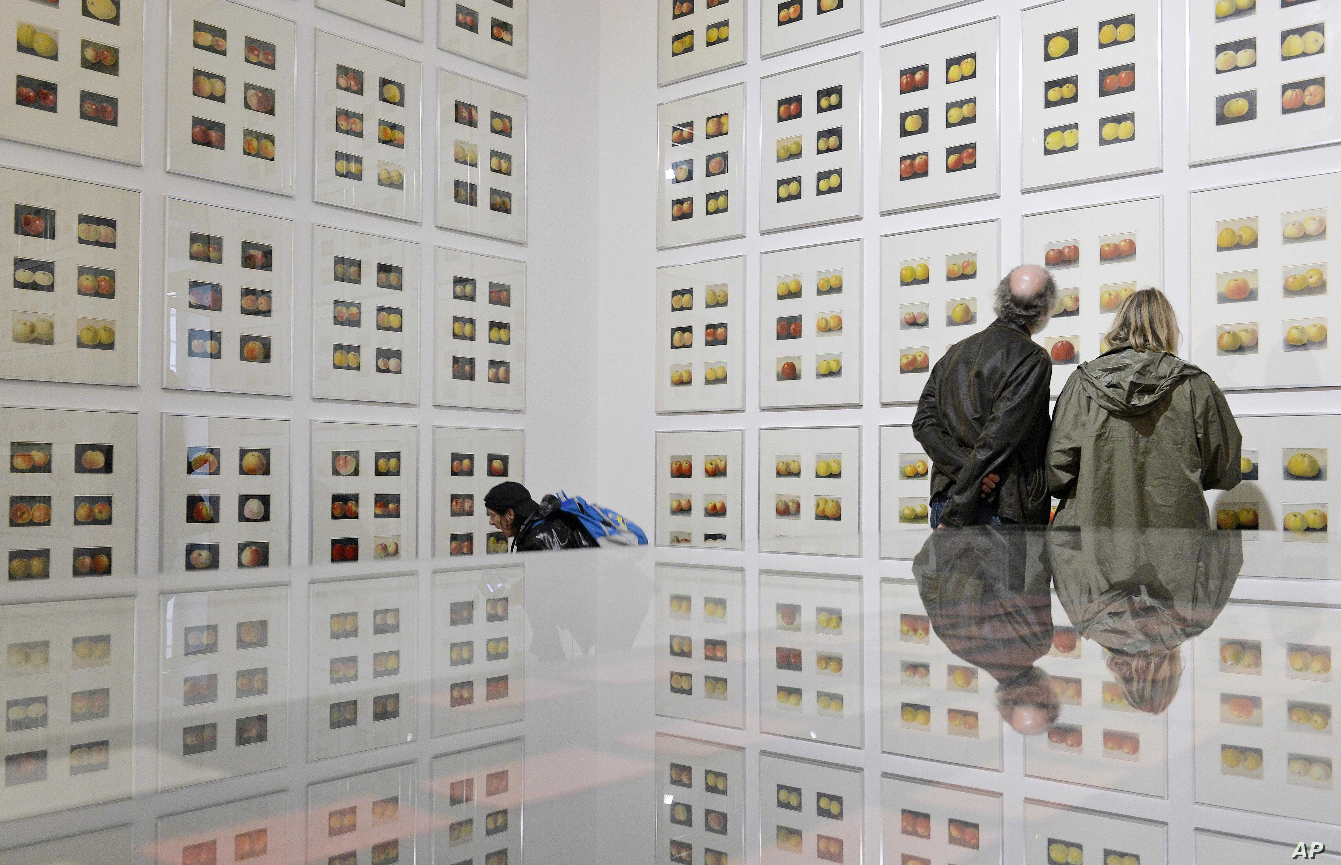 FILE - People stand in front of 372 drawings with the title '1912-60s' of German artist Korbinian Aigner during the press preview of the dOCUMENTA (13)in Kassel, Germany, June 6, 2012.