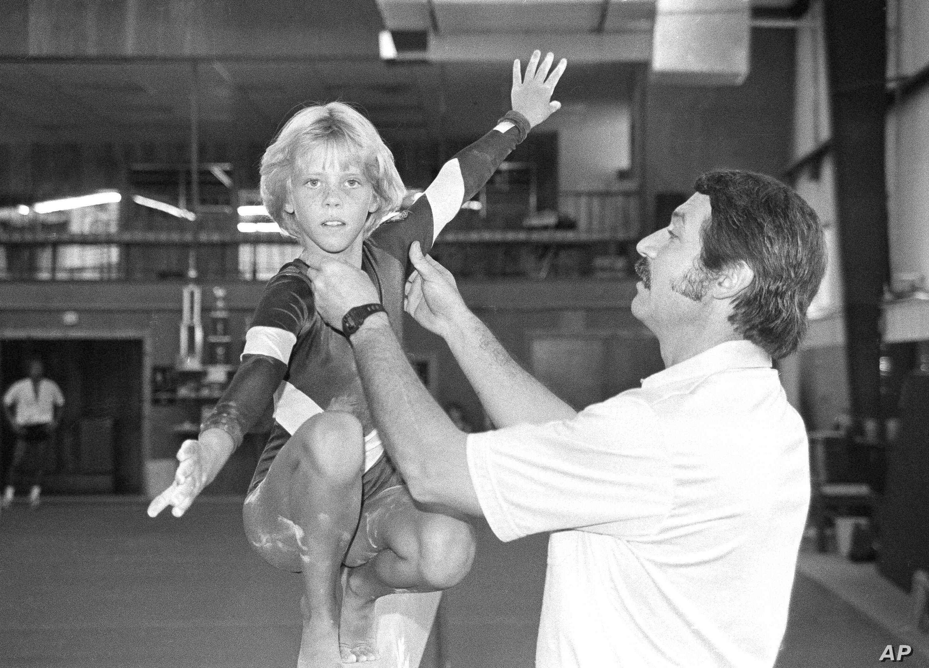 "FILE - In this Aug. 12, 1985, photo, coach Bela Karolyi, right, instructs Sara Tank on the balance beam. When Tank arrived in Houston in 1985, she soon realized that the Bela Karolyi she had seen on television, who was ""animated and acted like he lov..."