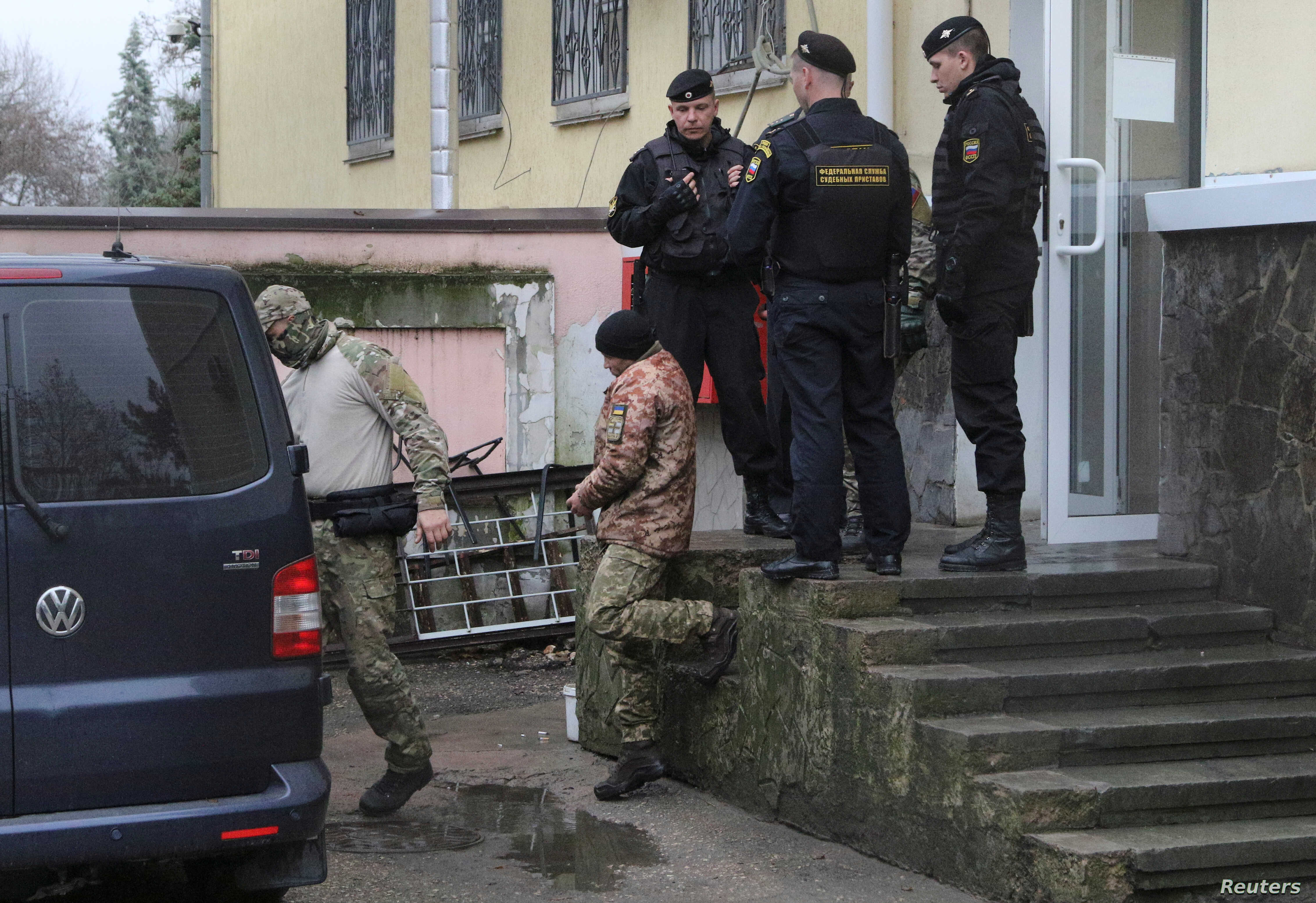 A crew member (C) of one of three Ukrainian naval ships, which were attacked and seized by Russia Sunday, is escorted after a court hearing in Simferopol, in Russia-annexed Crimea, Nov. 27, 2018.