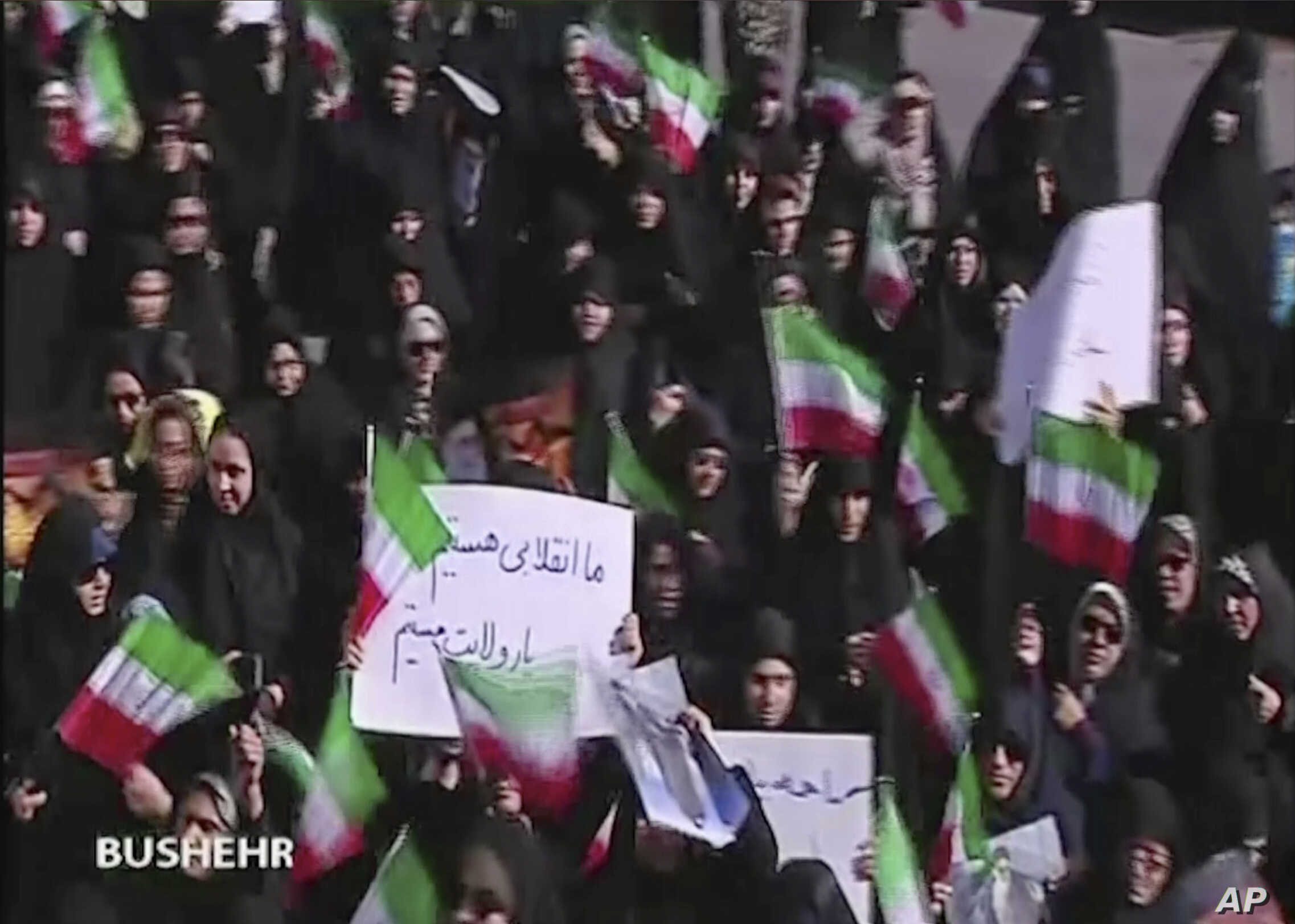 This frame grab from video provided by Iran Press, a pro-government news agency based in Beirut, shows pro-government demonstrators marching in Bushehr, Iran, Jan. 3, 2018.