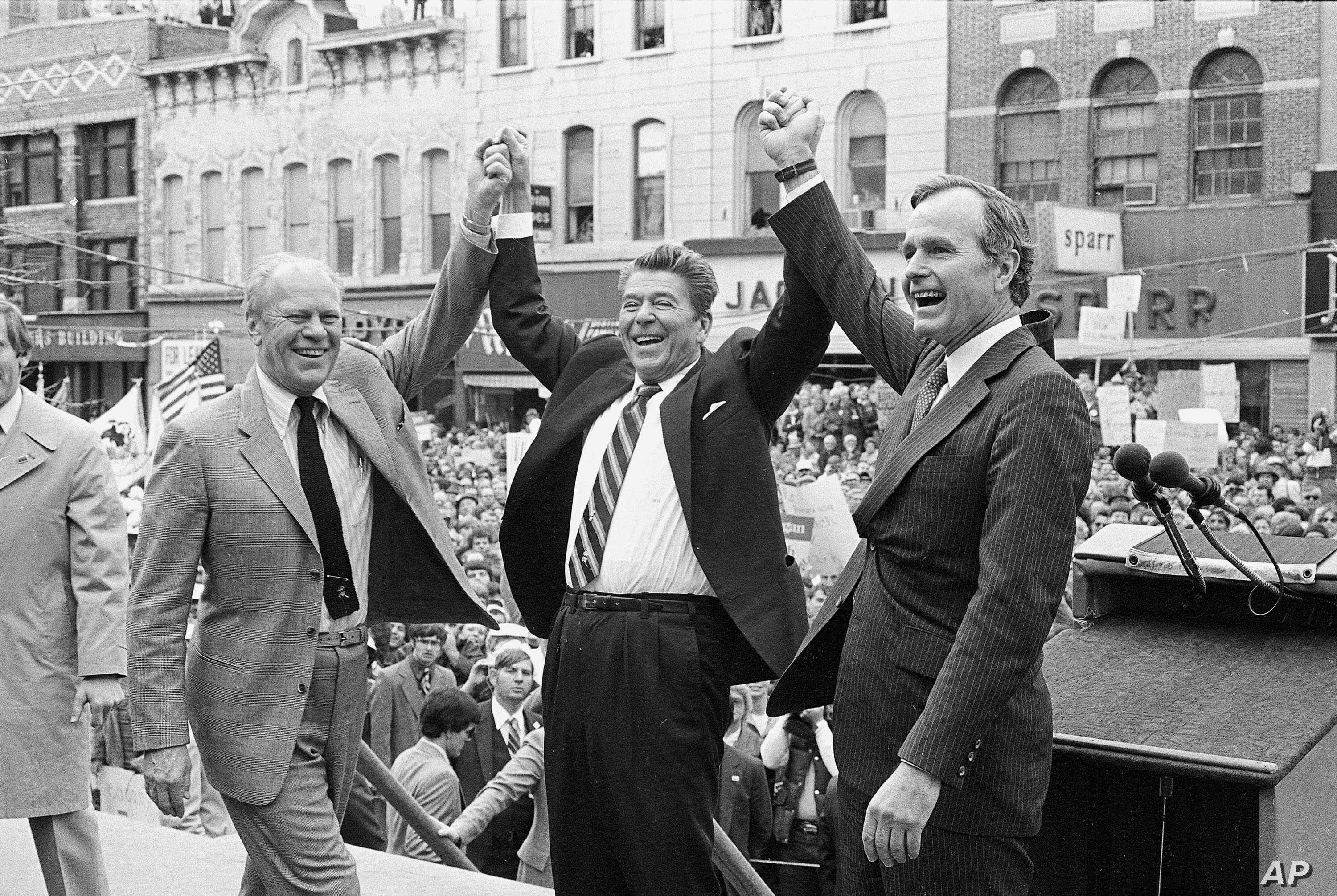 Former president Gerald Ford, left, lends his support to fellow Republican and presidential candidate Ronald Reagan and running mate George Bush, seen here on the final day of campaining in Peoria, Ill., on November 3, 1980.