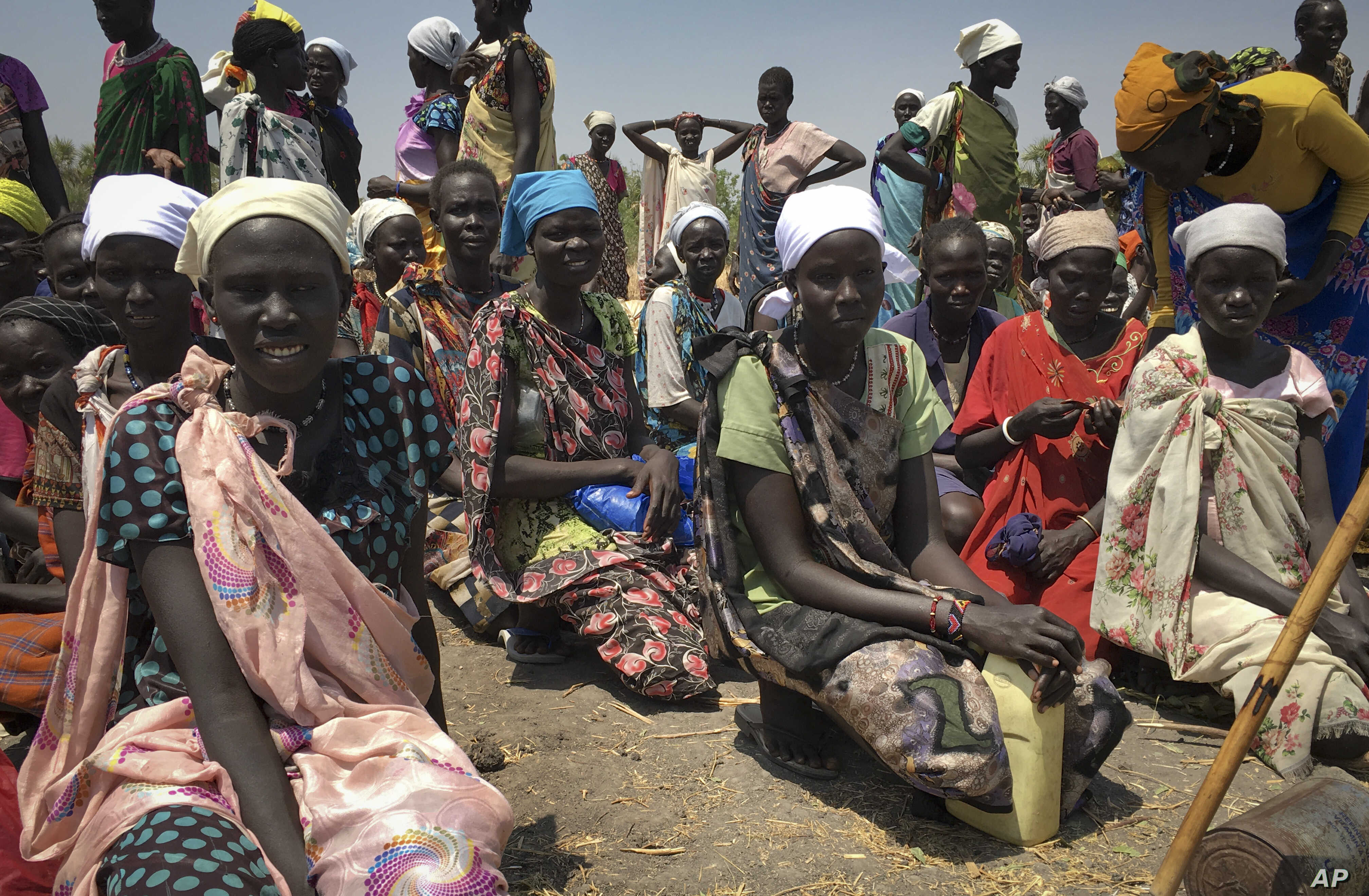 FILE - women sit in line on the ground waiting to receive food distributed by the World Food Program (WFP) in Padeah, South Sudan.