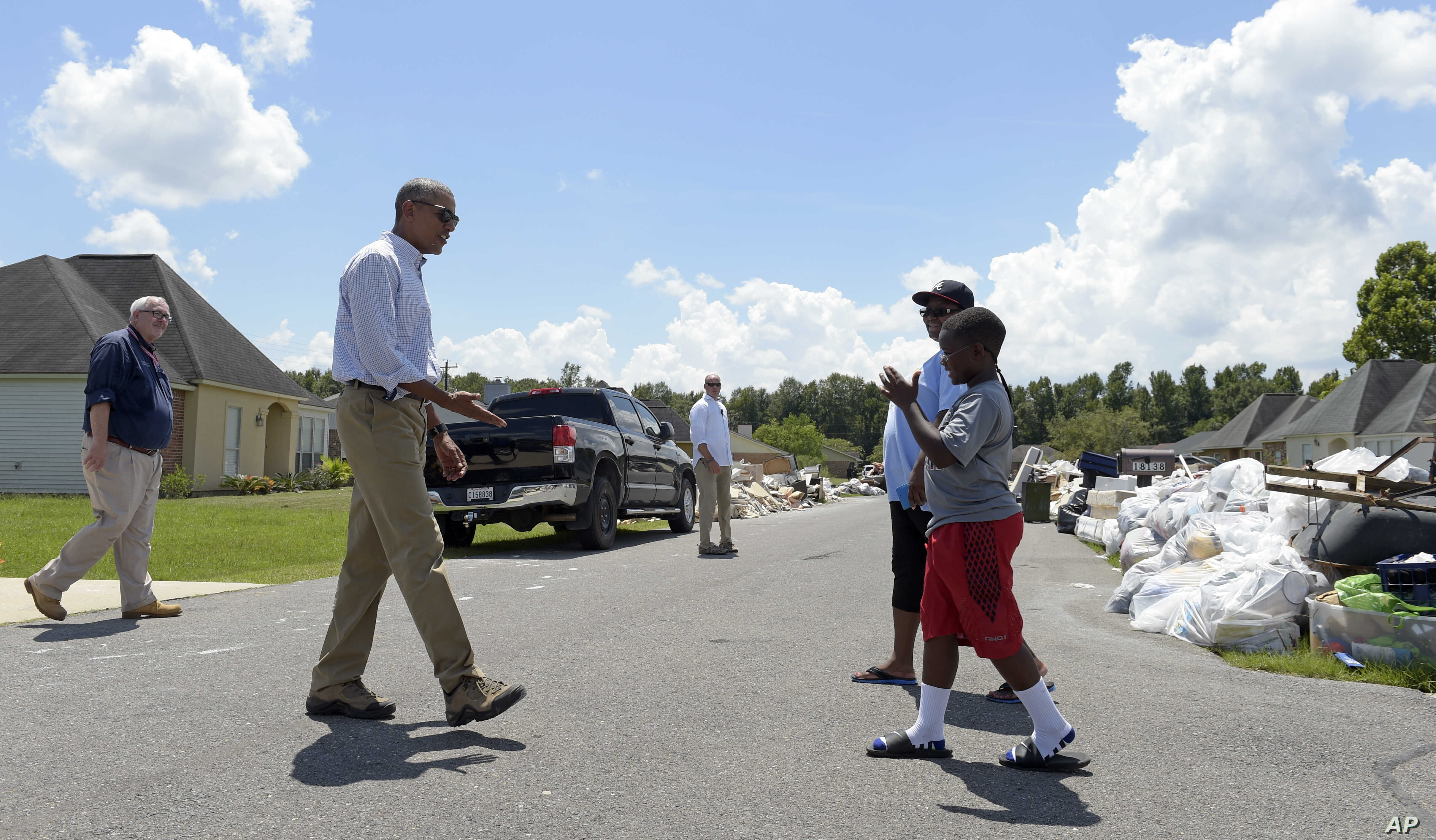 President Barack Obama walks to greet a family to tour their flood-damaged home in the Castle Place neighborhood of Baton Rouge, La., Aug. 23, 2016.