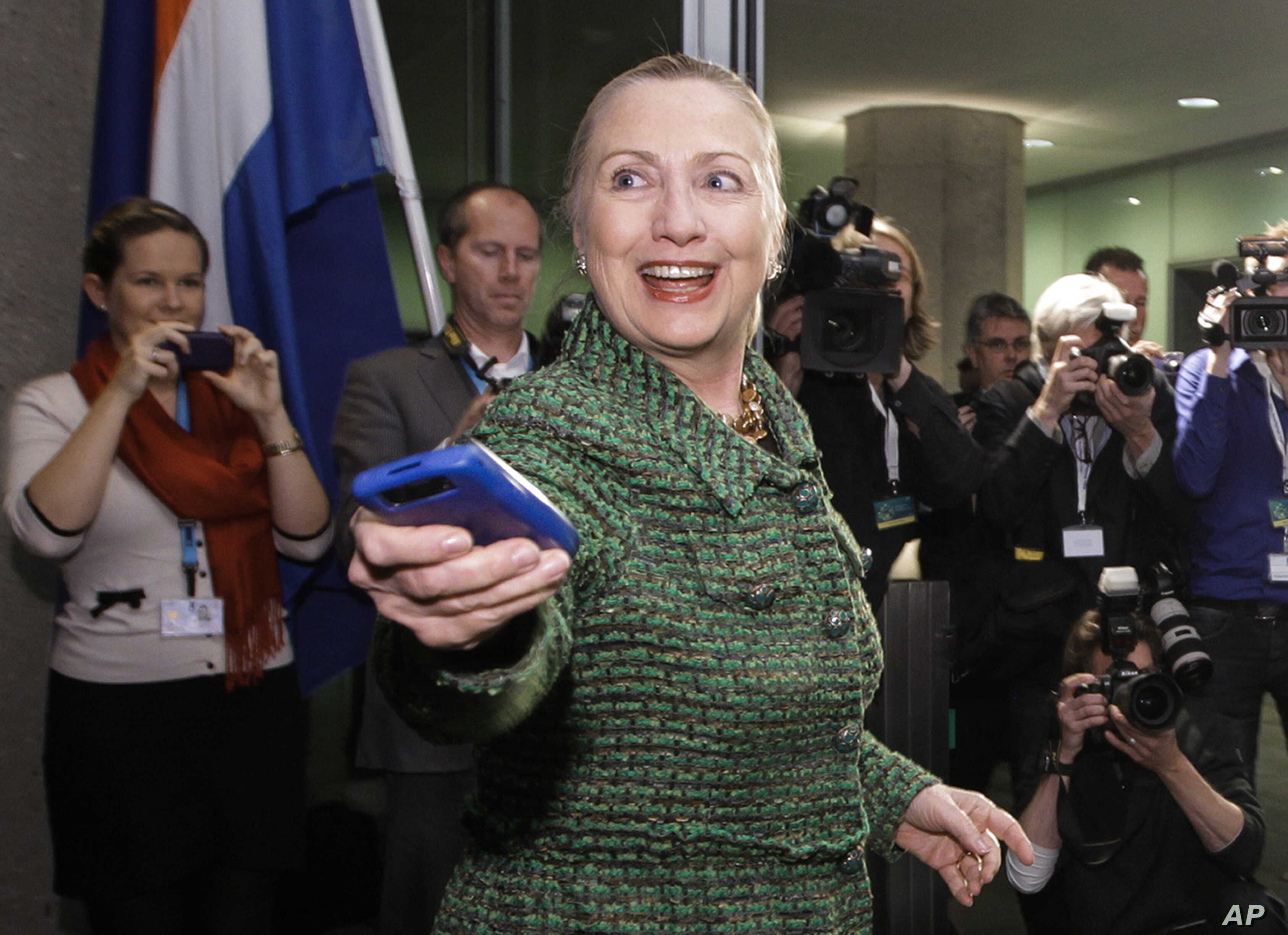 FILE -  Then-U.S. Secretary of State Hillary Clinton hands off her mobile phone after arriving to meet with Dutch Foreign Minister Uri Rosenthal at the Ministry of Foreign Affairs in The Hague, Netherlands, Dec. 8, 2011.