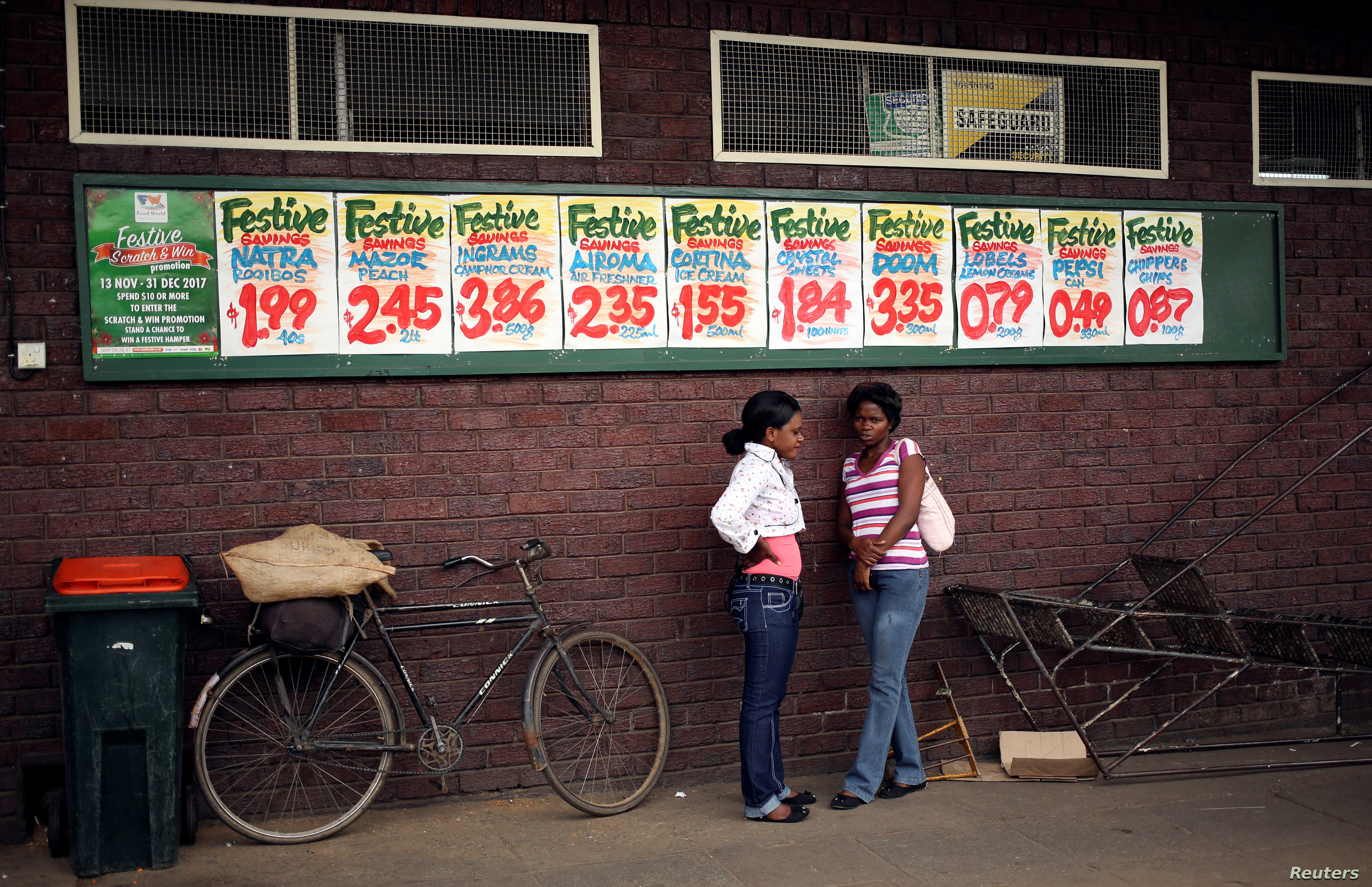 Women chat near posters advertising food prices outside a shop in Harare, Zimbabwe, Nov. 25, 2017.