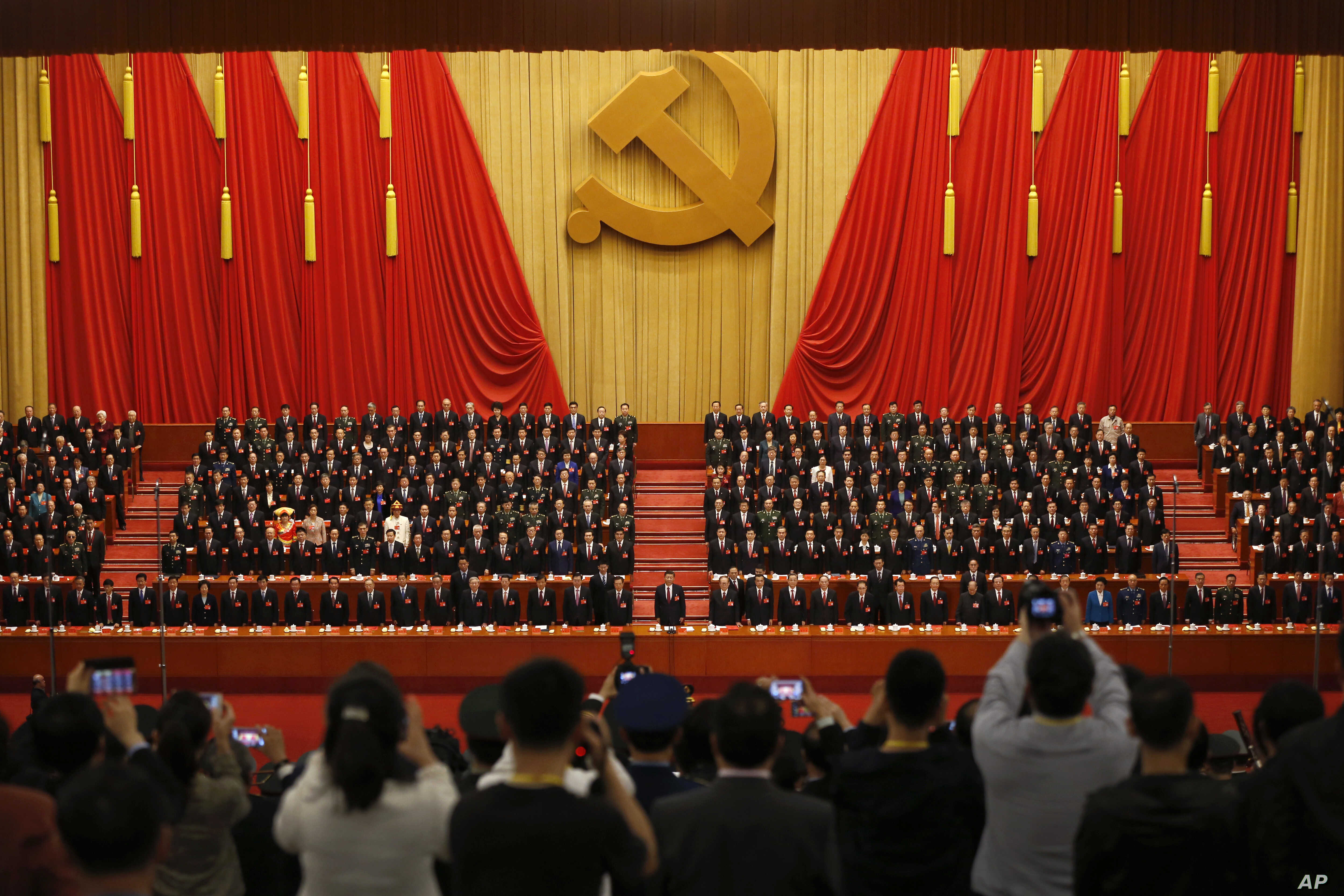 FILE - Journalists take pictures of Chinese President Xi Jinping, front row center, and other Communist Party officials at Party Congress at the Great Hall of the People in Beijing, Oct. 24, 2017.
