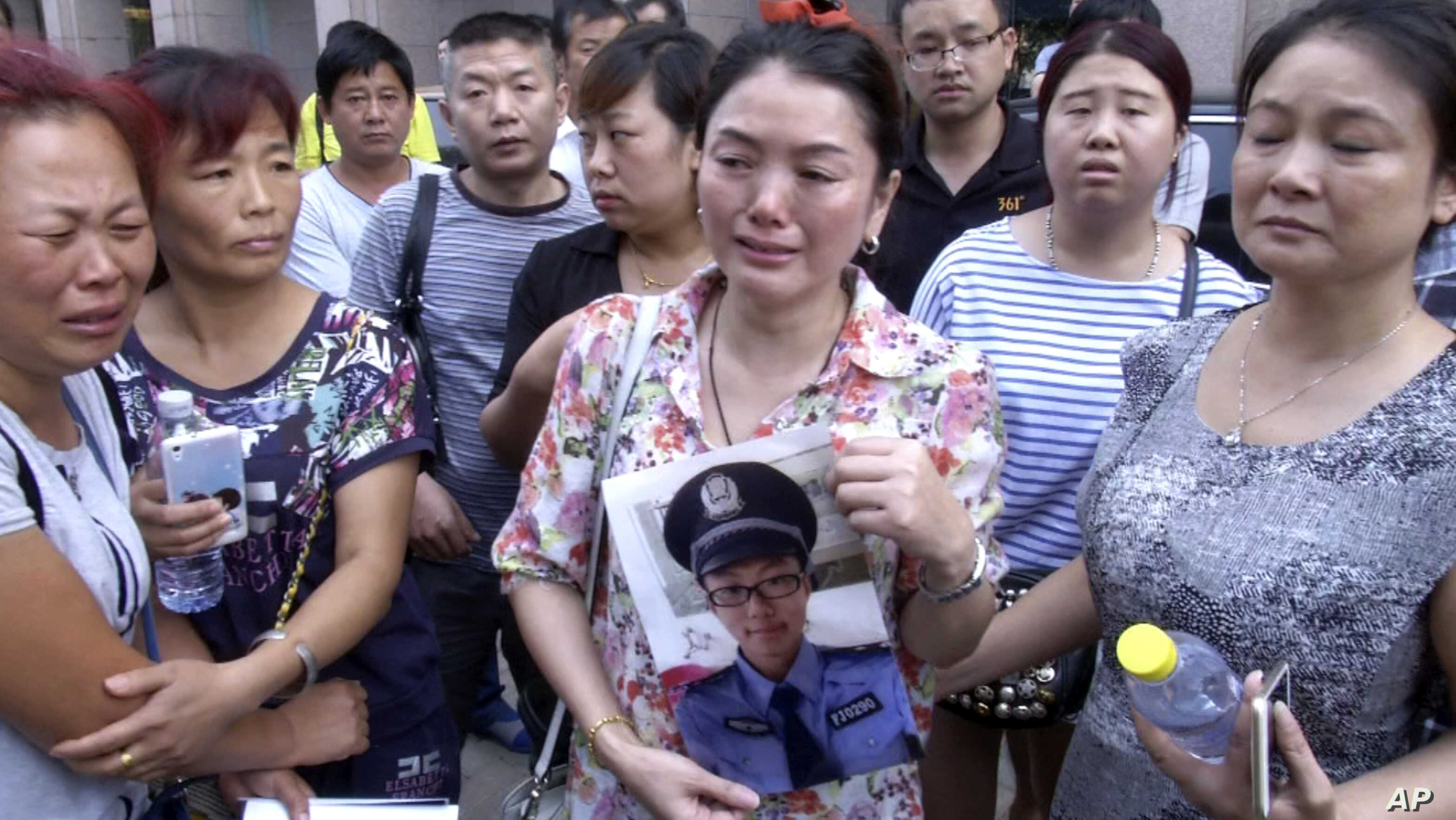 In this image taken from a video footage from AP Video, a woman holds up a photo of her son, a missing firefighter, outside a hotel where officials held a daily media conferences in northeastern China's Tianjin municipality, Aug. 16, 2015.