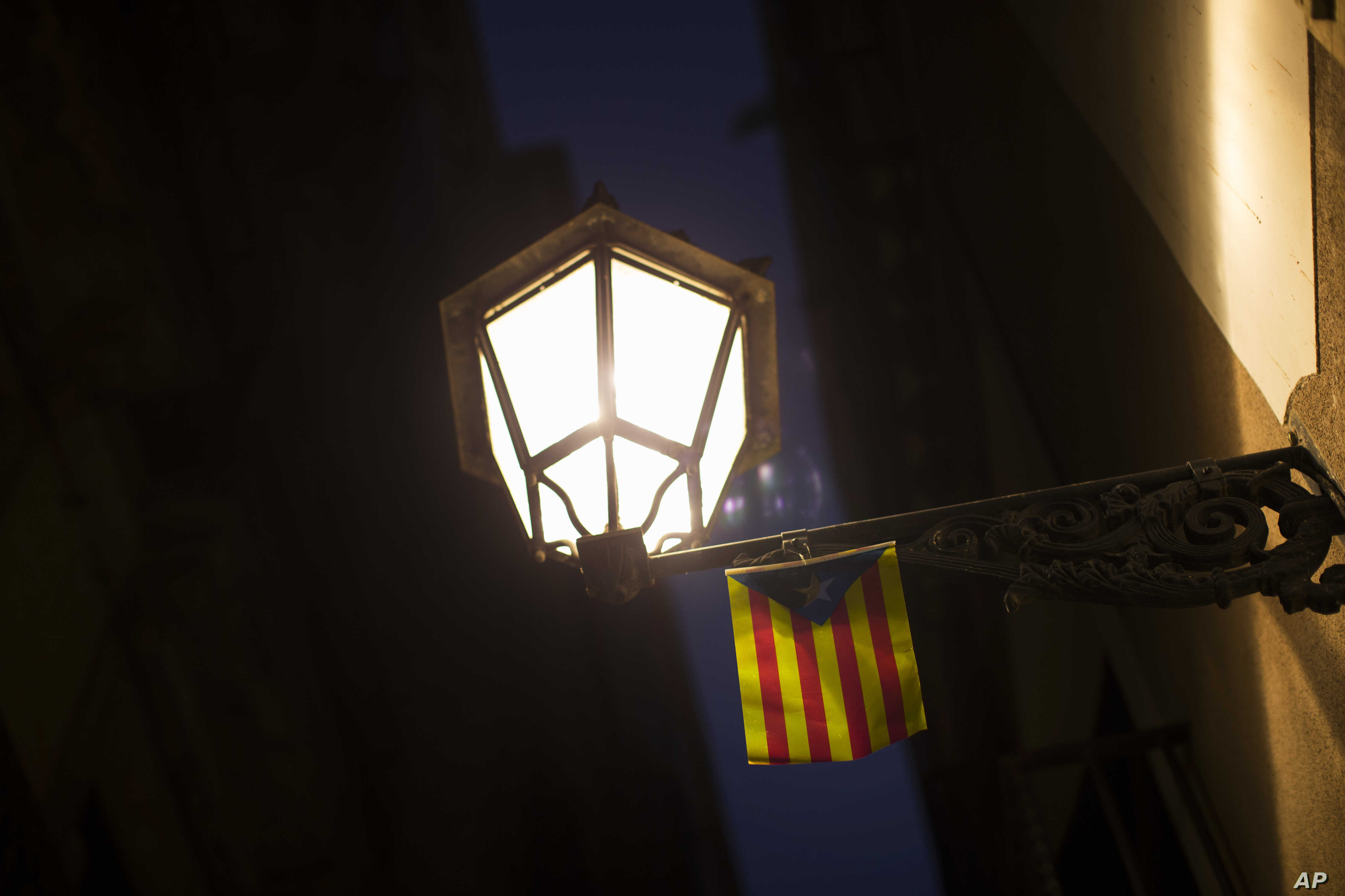"An ""estelada"", or Catalonia independence flag, hangs from a street light in downtown Barcelona, Oct. 6, 2017."