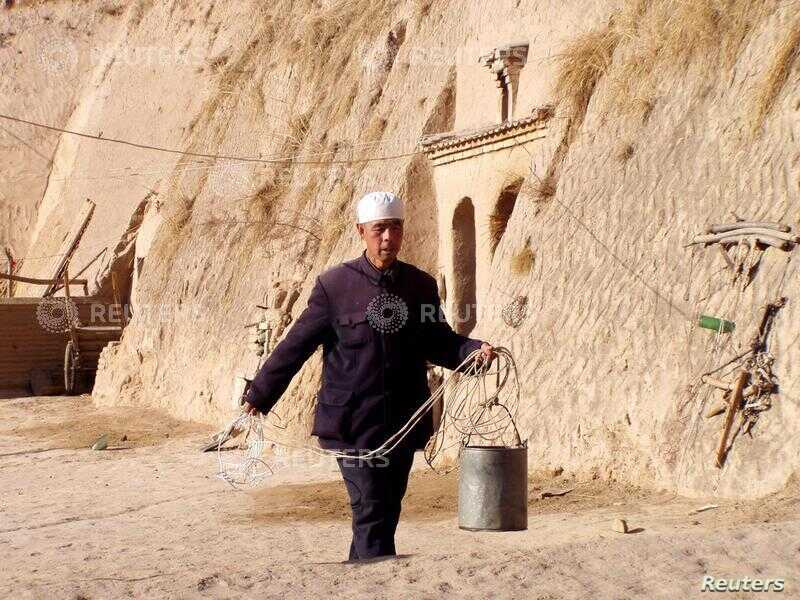 FILE - A villager in Tanshan, nestled among brown hills in central China's Ningxia region, walks to a well to fetch water Feb. 17, 2003.