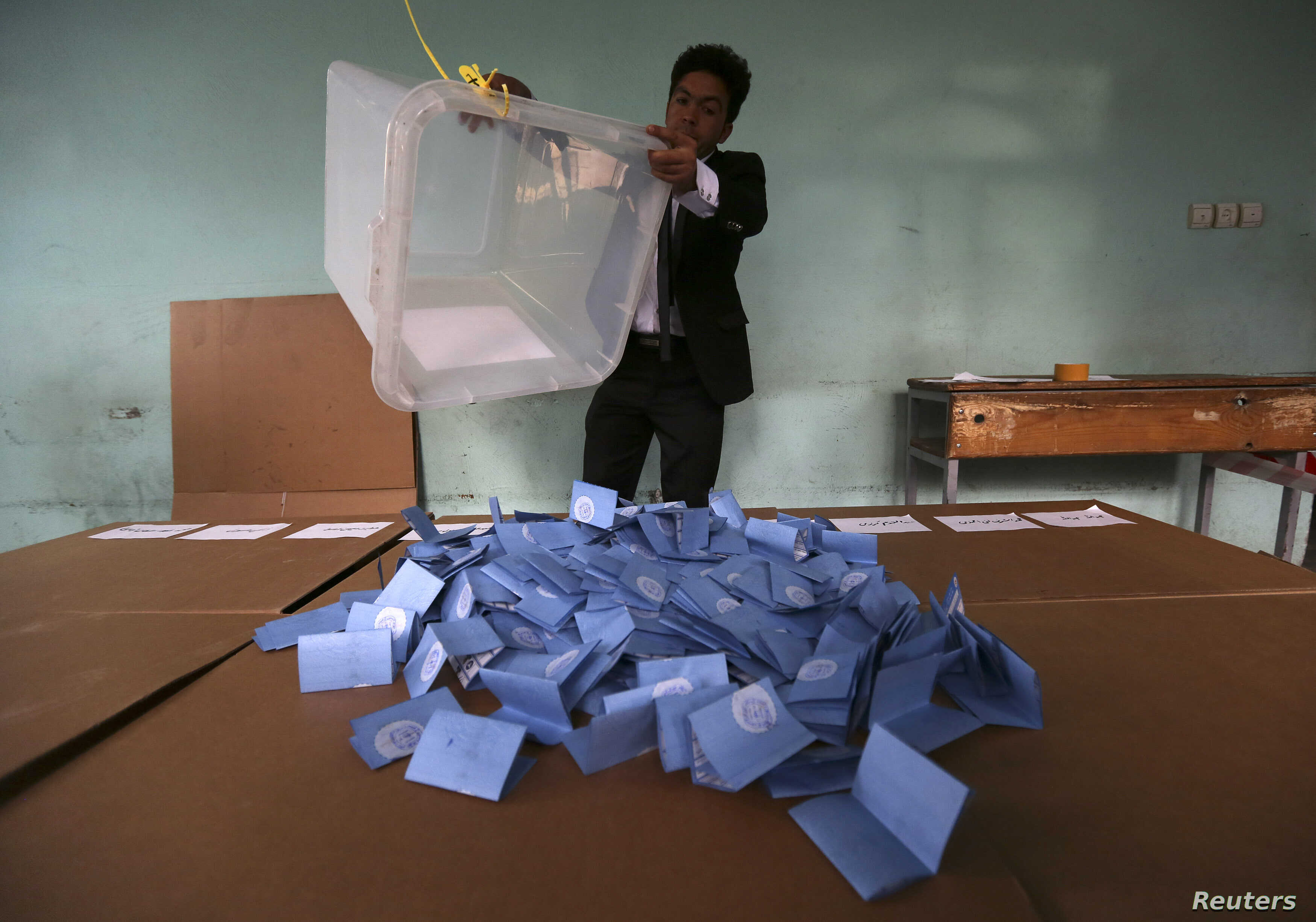 An Afghan election official empties a ballot box for counting at the end of polling in Herat Province, Apr. 5, 2014.