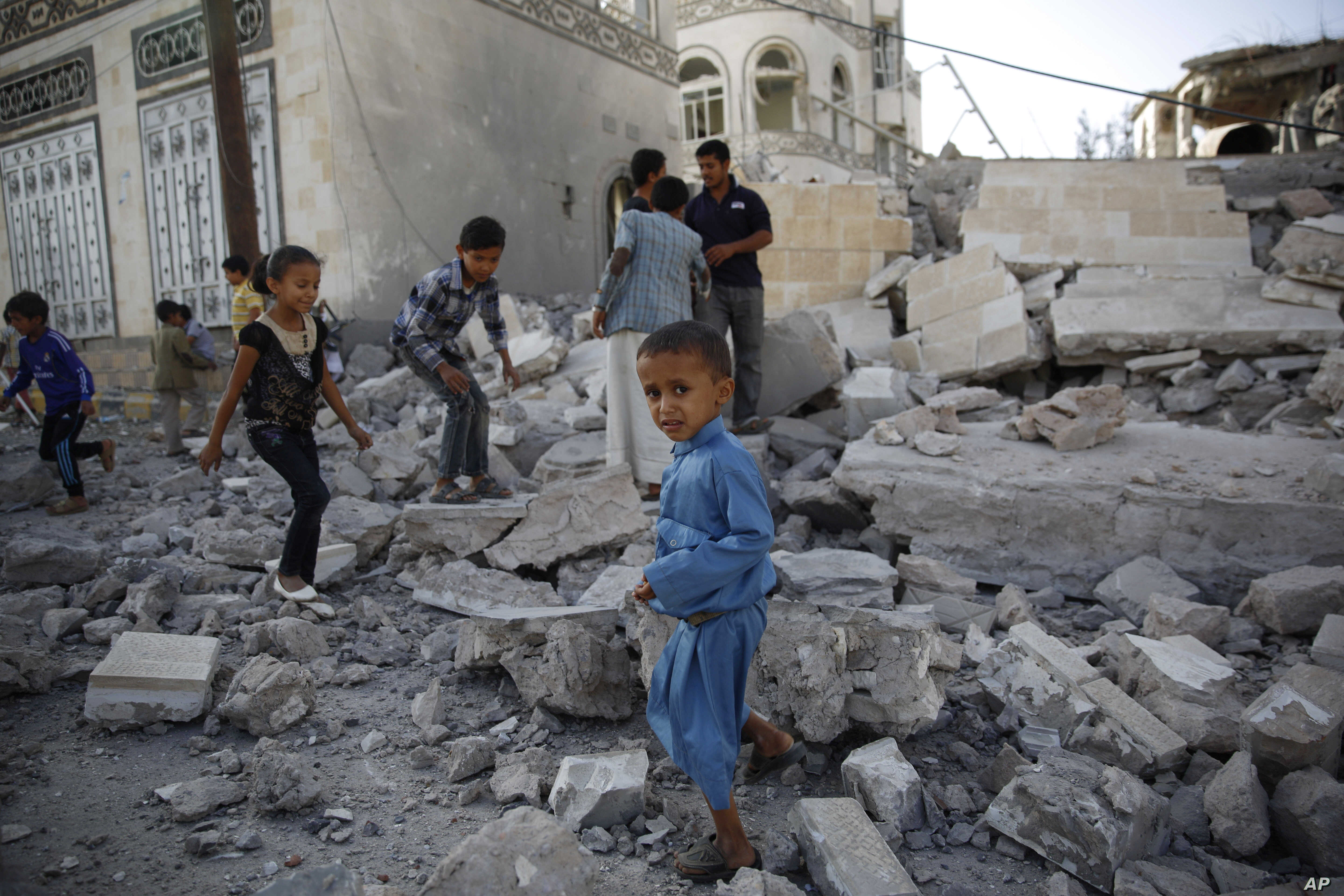 FILE - Children play amid the rubble of a house destroyed by a Saudi-led airstrike in Sana'a, Yemen, Sept. 8, 2015. A cease-fire declared two months ago has not slowed the violence the Yemen, local activists say.