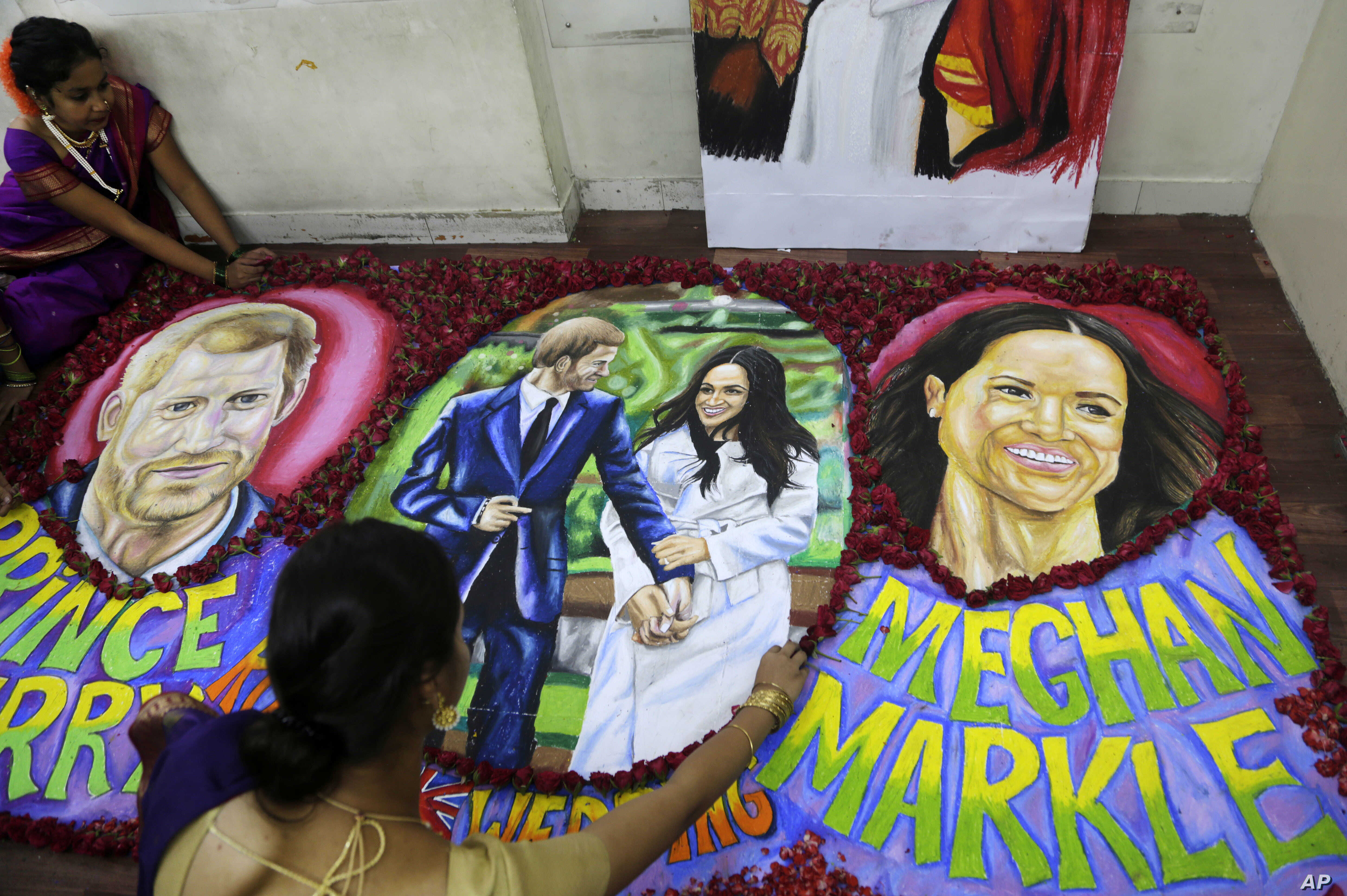 Students of an art school decorate paintings of Britain's Prince Harry and Meghan Markle with flower petals in Mumbai, India, May 18, 2018. The royal wedding is set for May 19 at England's Windsor Castle.